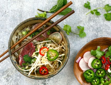 Bowl of Instant Pot beef pho with garnishes.