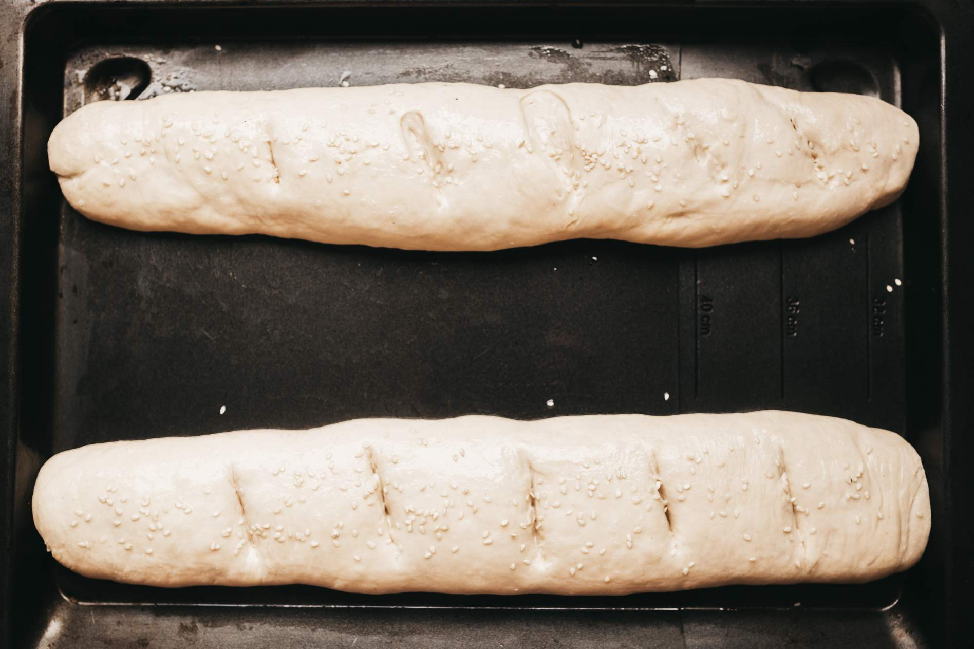 Loaves brushed with egg white and sesame seeds added