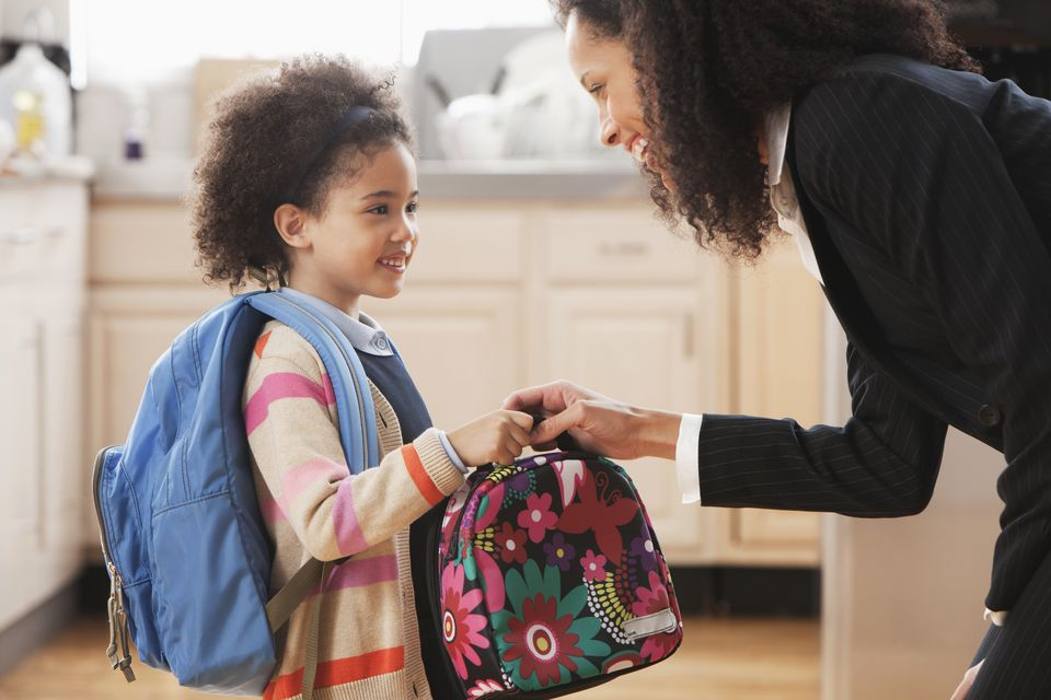 Mixed race mother handing lunch box to daughter
