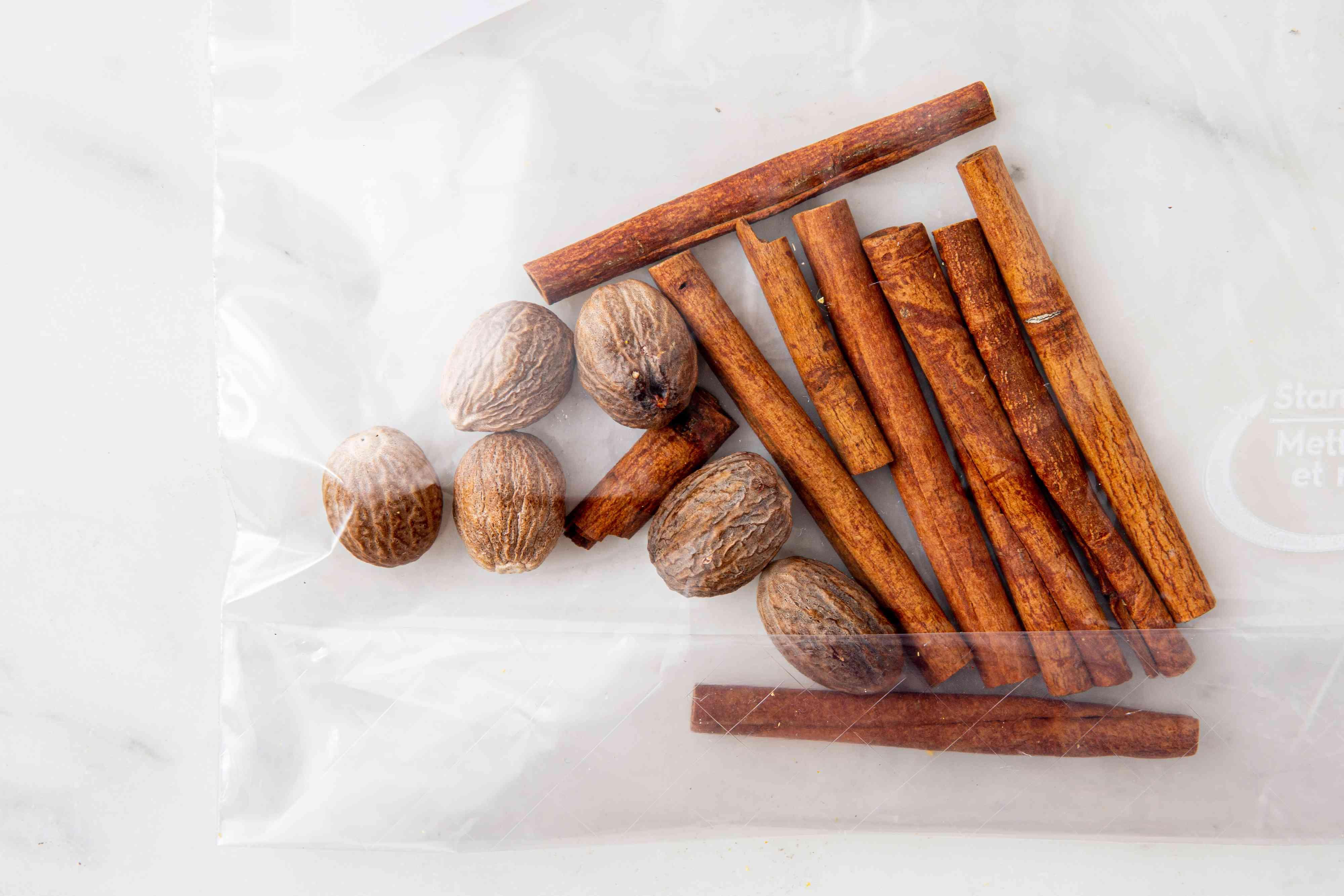 cinnamon sticks and nutmeg in a heavy-duty freezer bag
