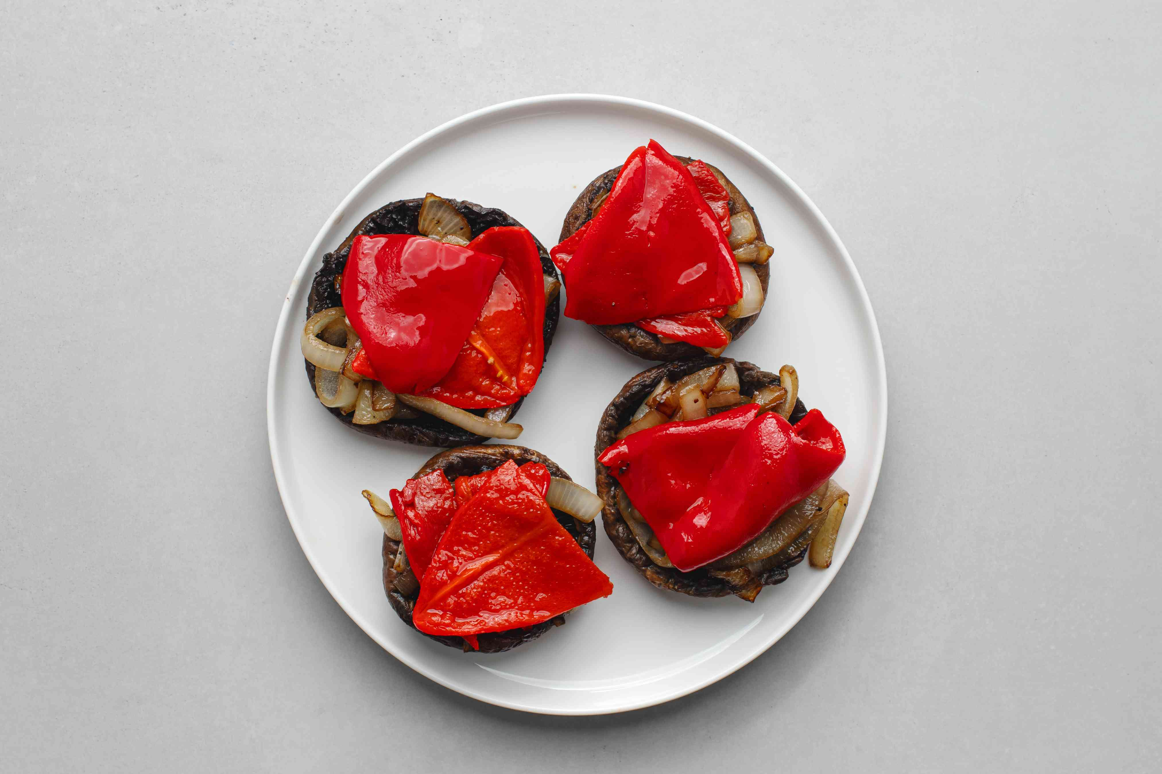 spoon the onions and roasted red peppers into the grilled mushroom cavities