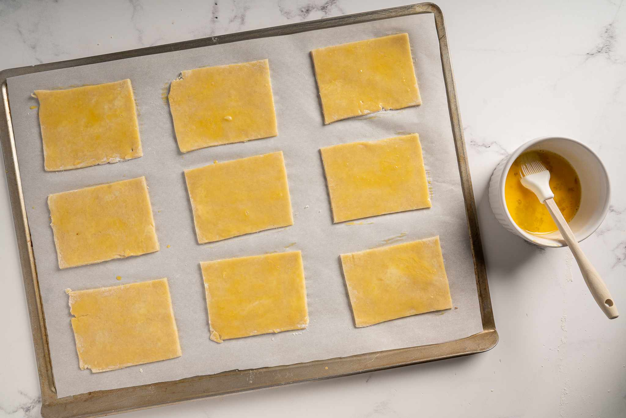 Pastry rectangles on a parchment-lined baking sheet brushed with egg