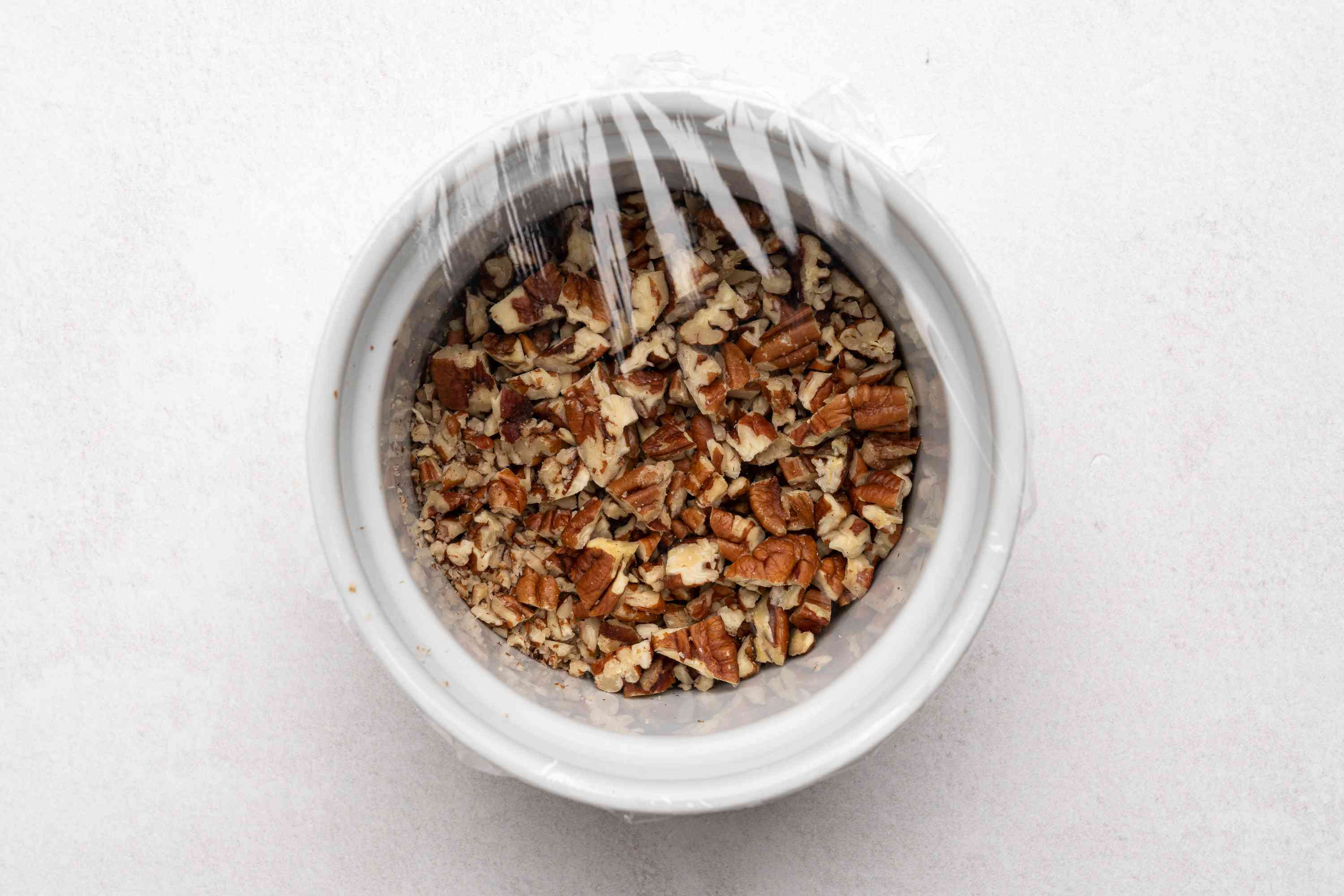 chopped pecans in a bowl covered with plastic wrap