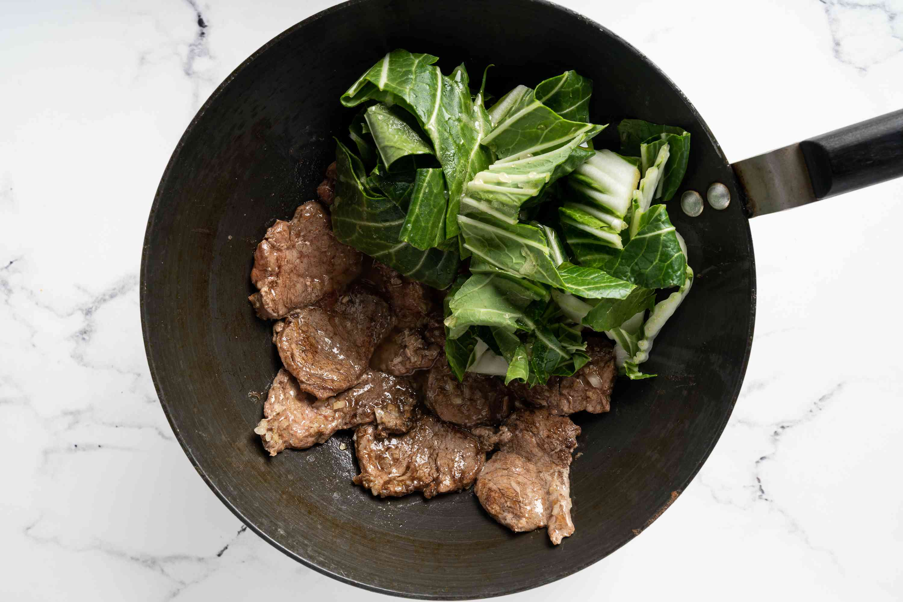 pork and bok choy cooking in a pan