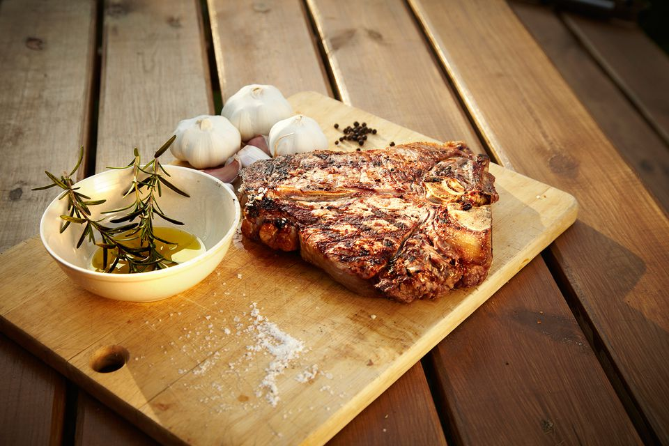 Steak grilled a la plancha served with garlic bulbs and a rosemary olive oil dipping sauce