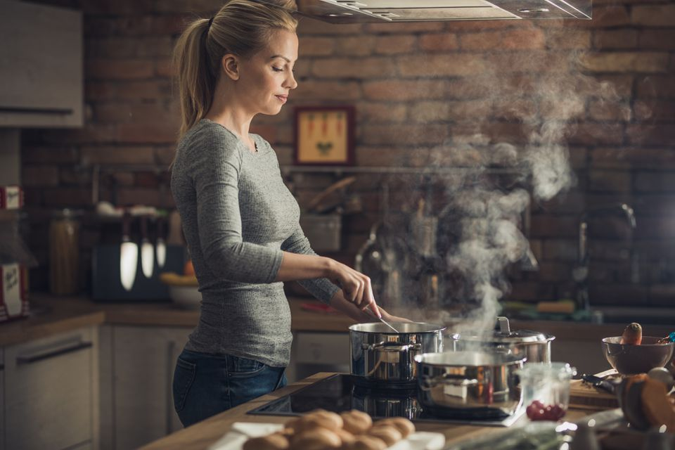 Young beautiful woman cooking lunch in the kitchen.
