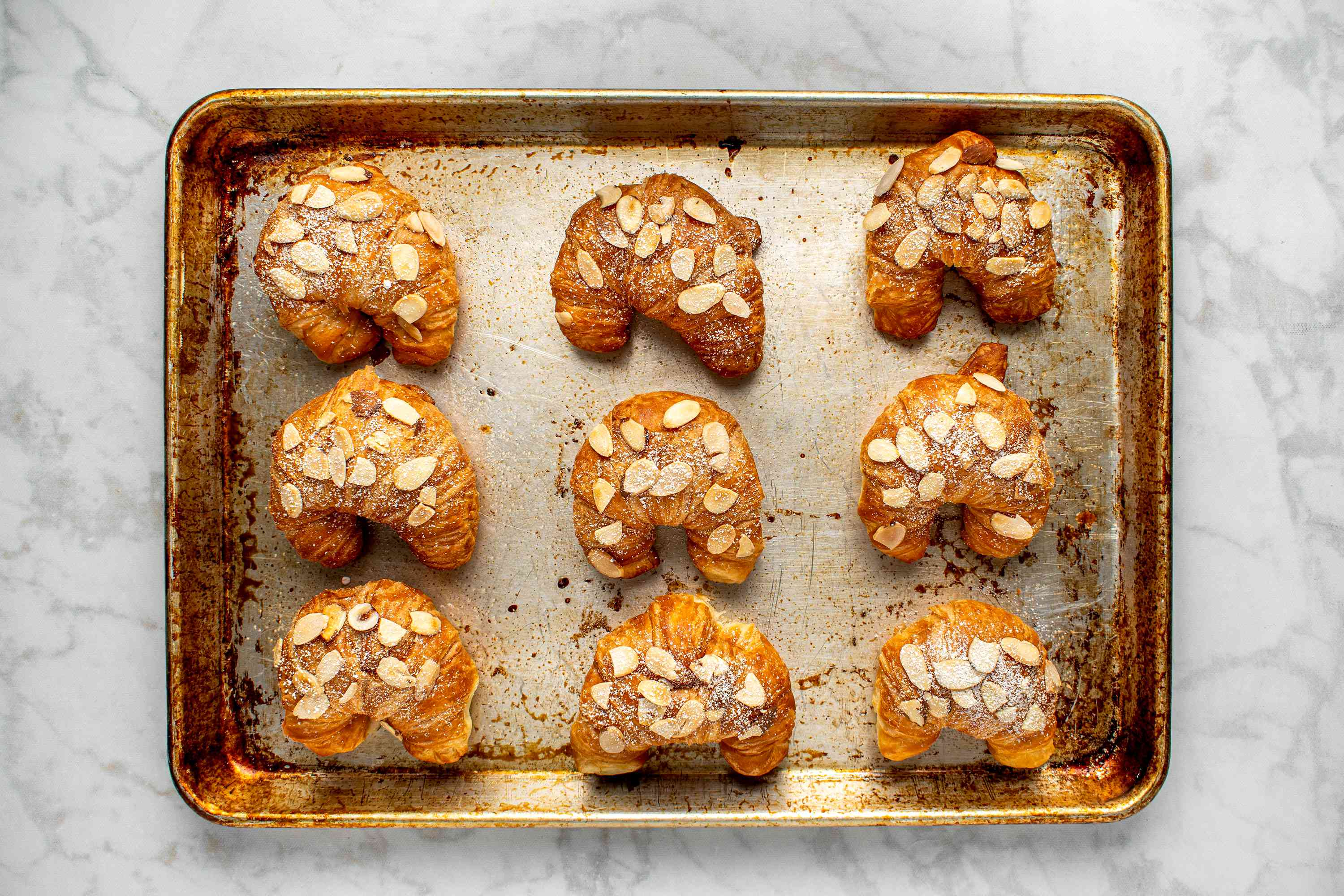 Classic French Almond Croissants topped with sugar on a baking sheet