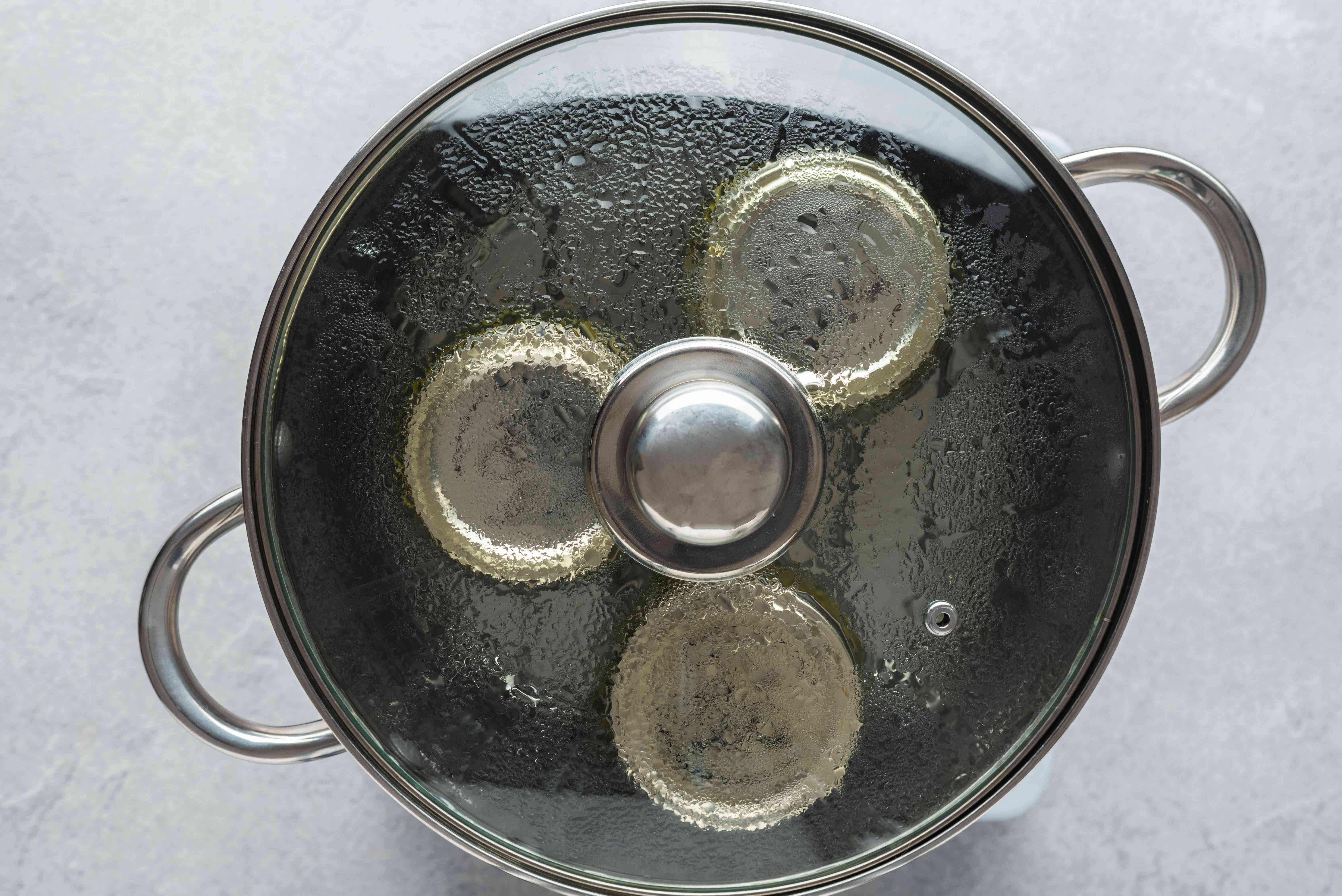 cans with cucumbers in the a water canner