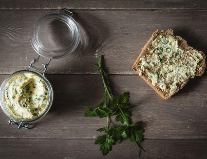 Herb butter, slice of spelt bread on wood