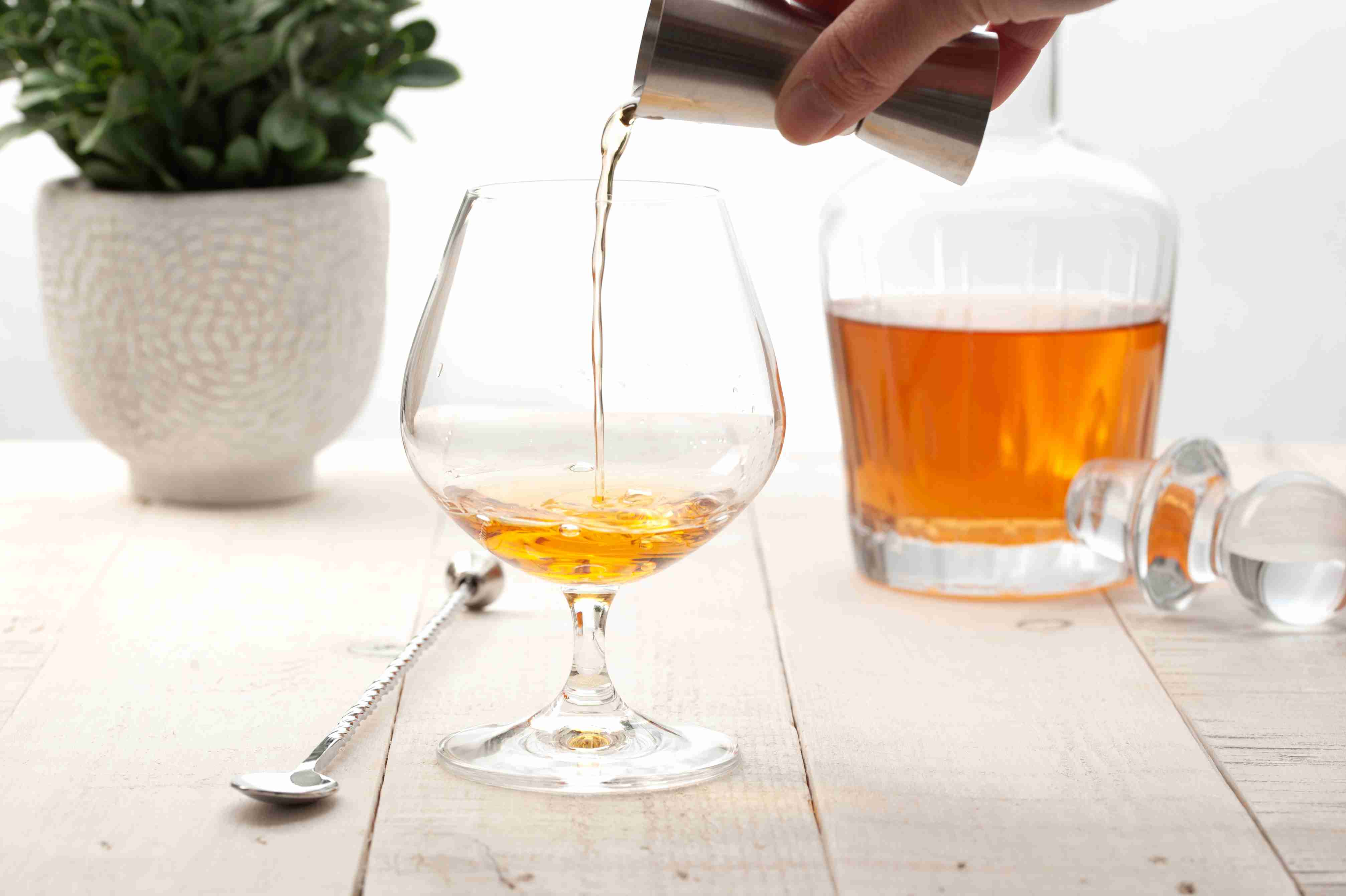 Pouring the brandy and Bénédictine into a snifter