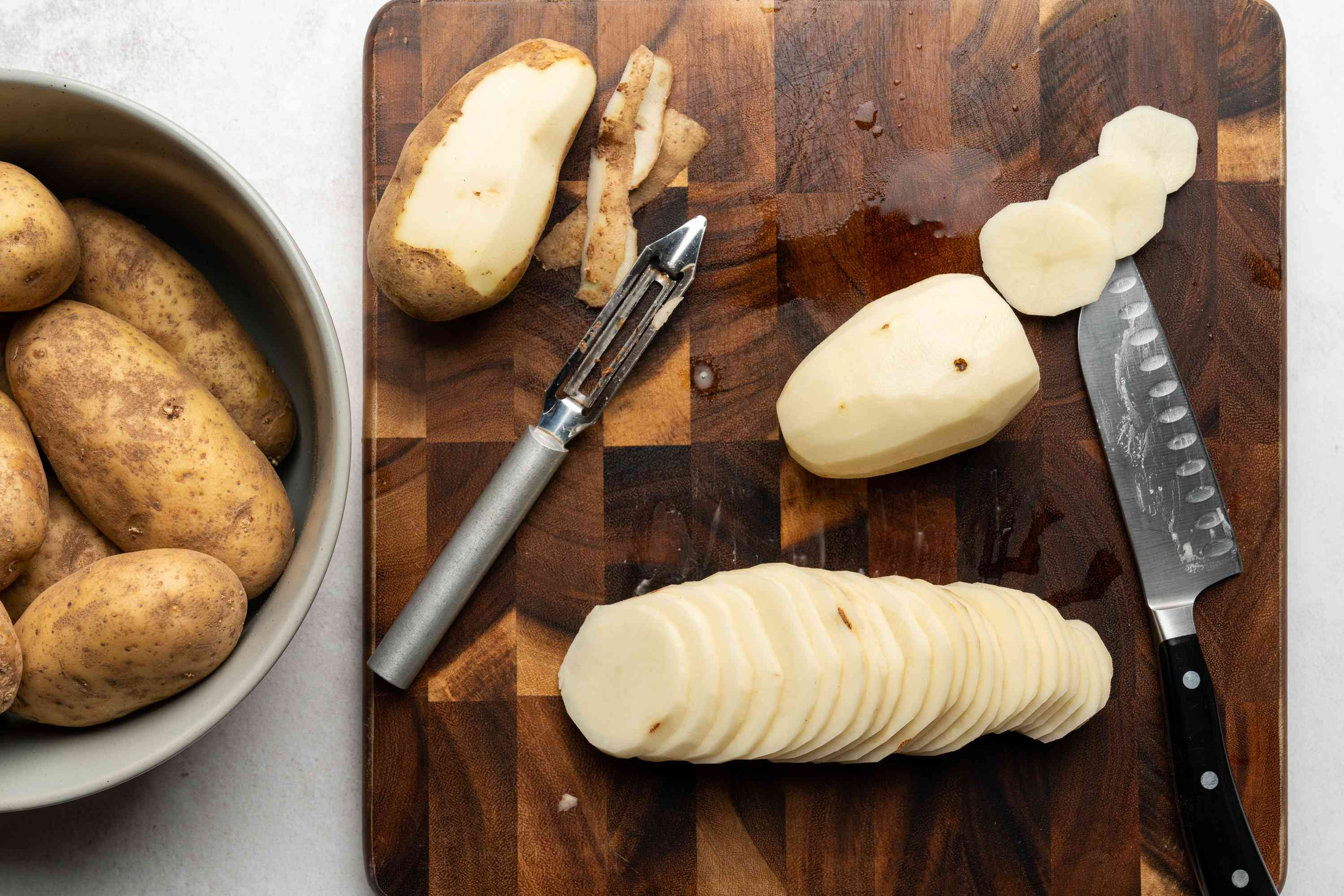 peeled and sliced potatoes on a cutting board