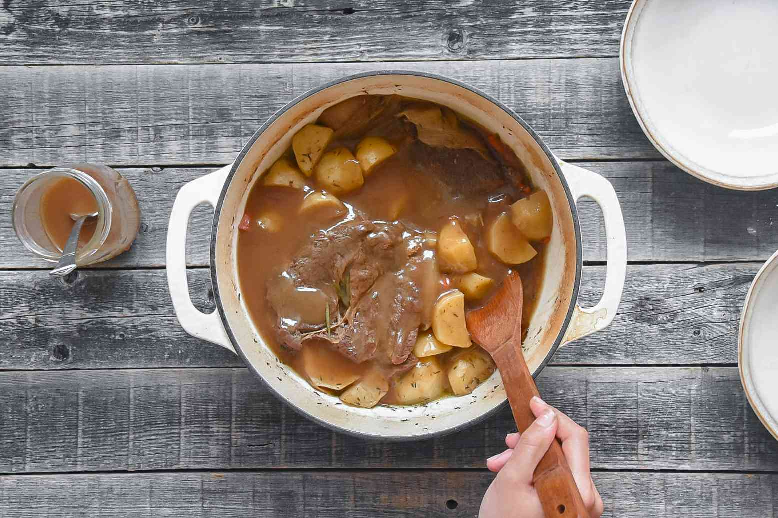 Gravy poured over the pot roast and vegetables in the large white pot