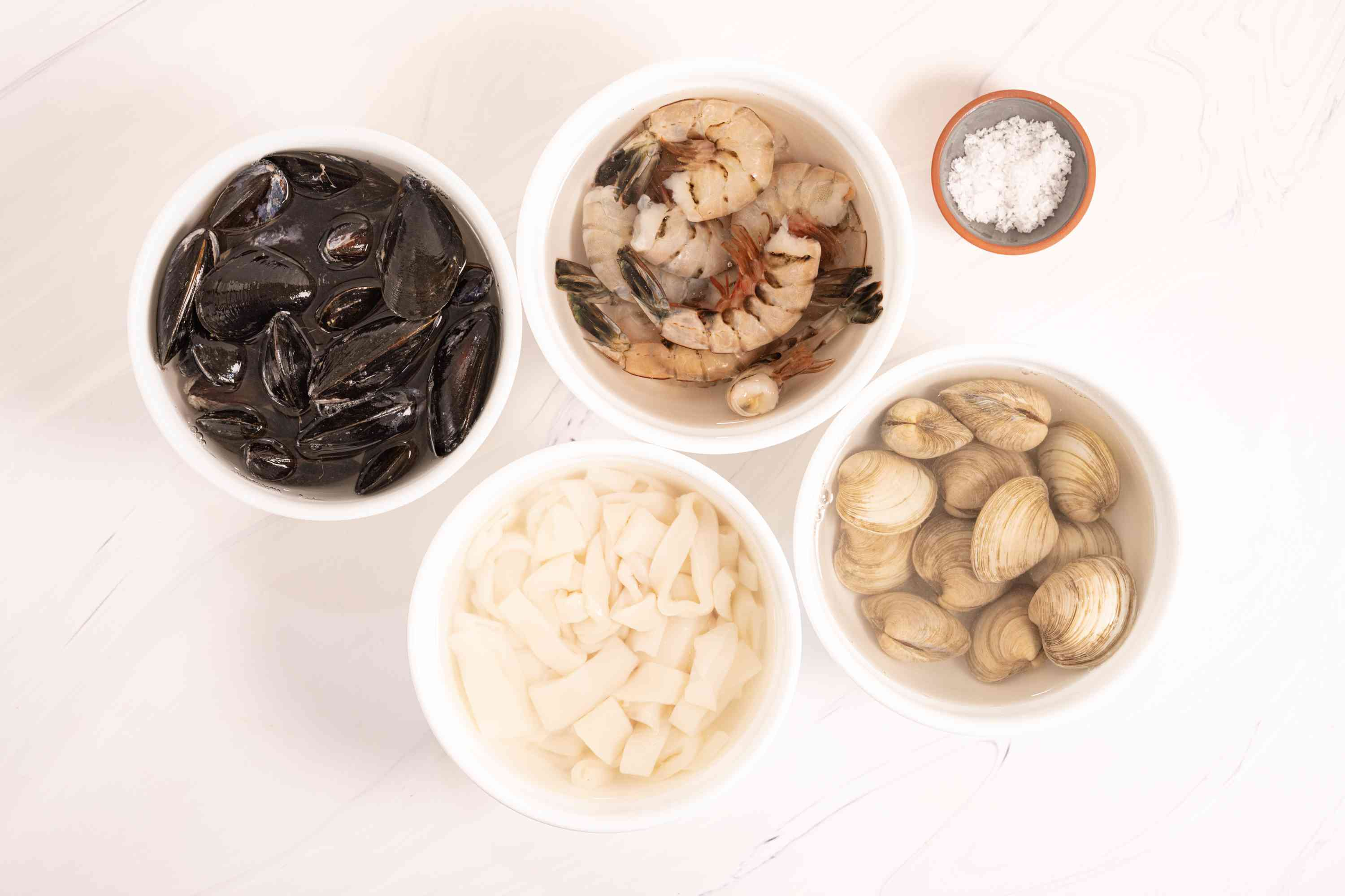 shrimp, squid, mussels, and small clams in 4 different bowls of cold water
