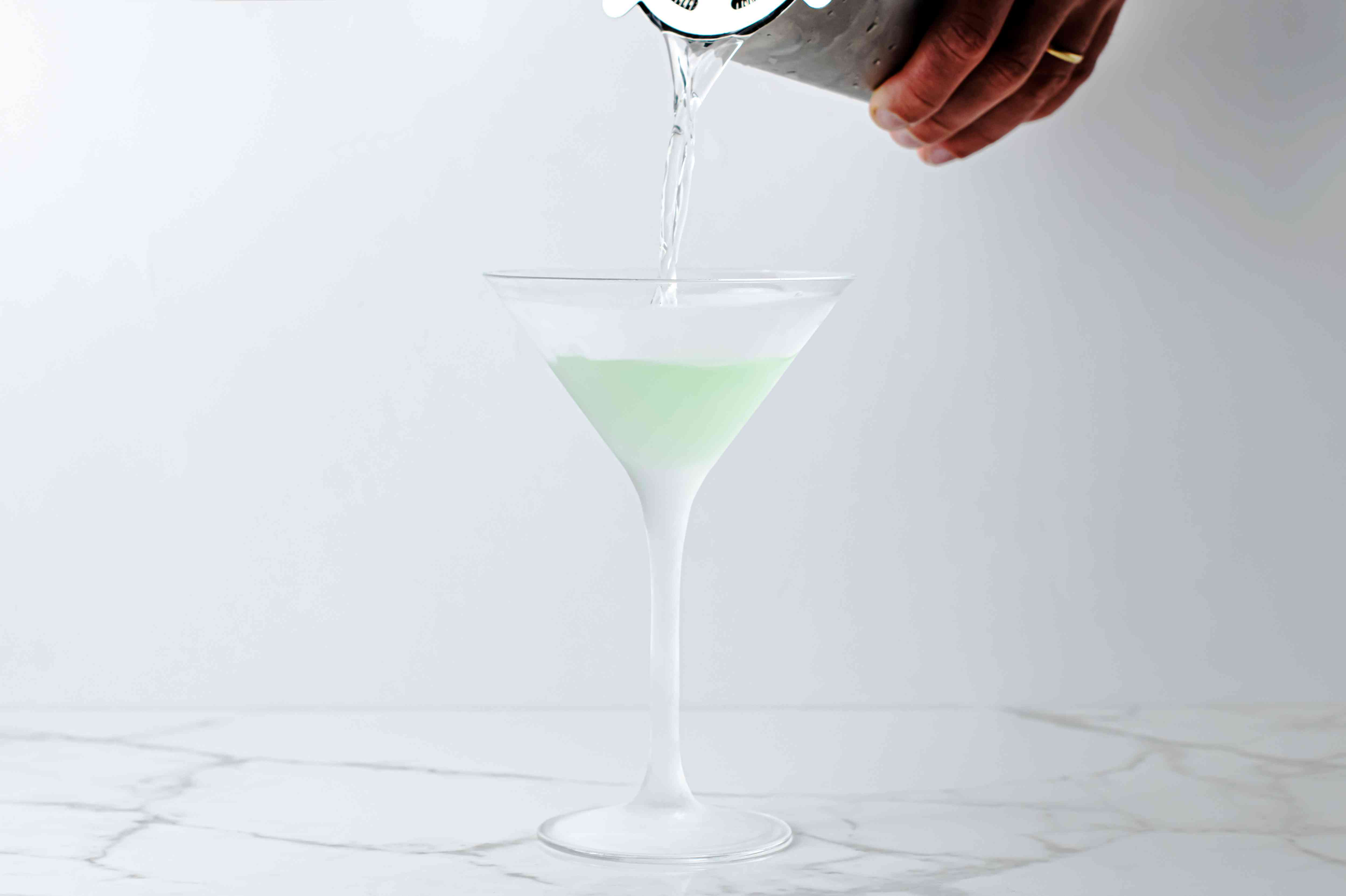 Pouring a green apple martini cocktail from a shaker into a glass