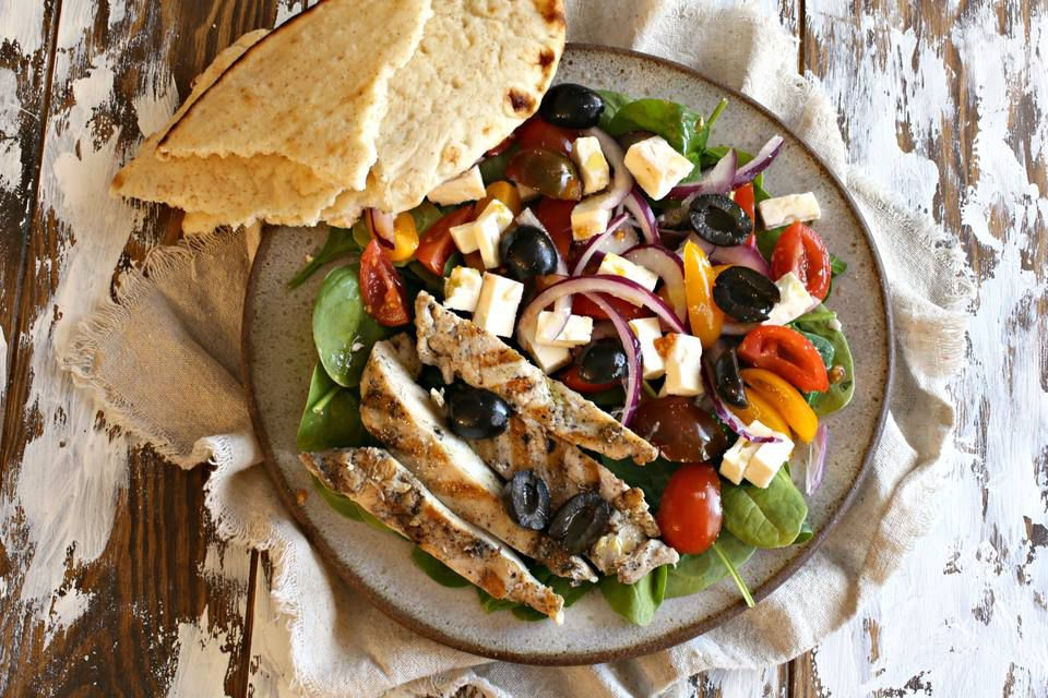 Serving of Mediterranean chicken salad with a side of toasted pita bread