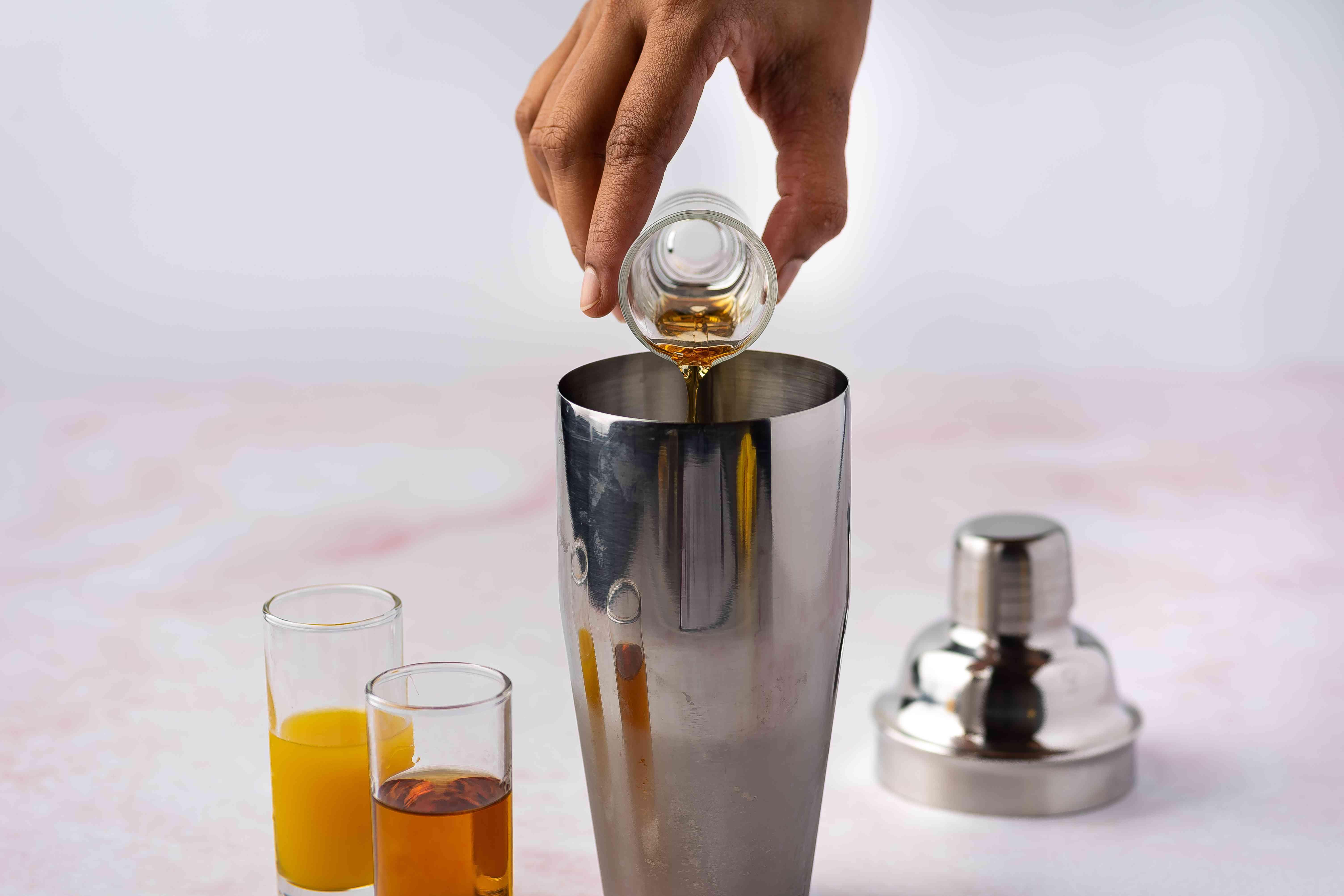 ice, cognac, orange liqueur, and orange juice in a cocktail shaker