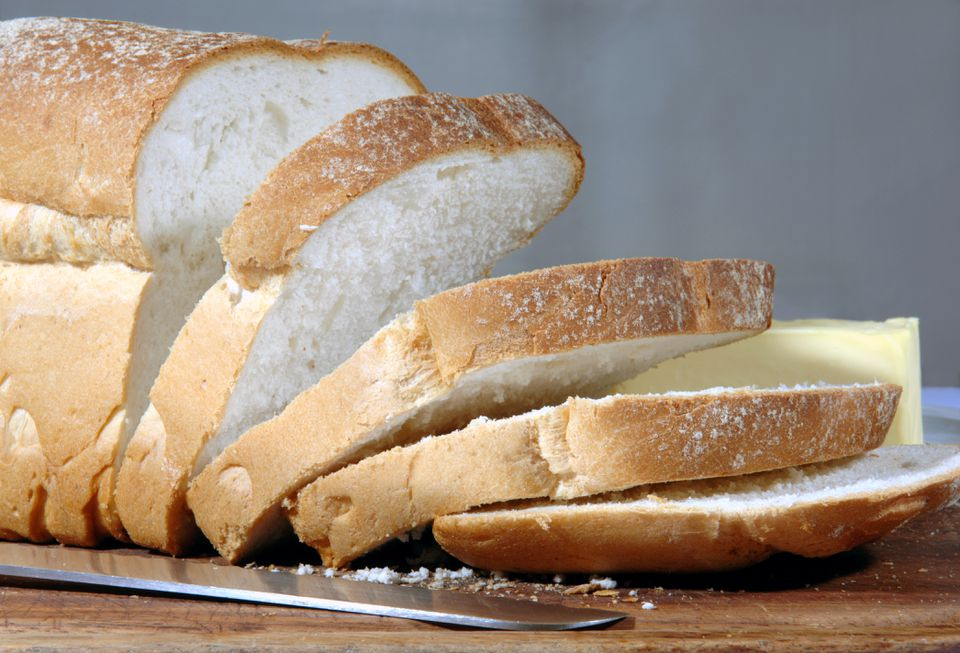 A partially sliced loaf of white bread.