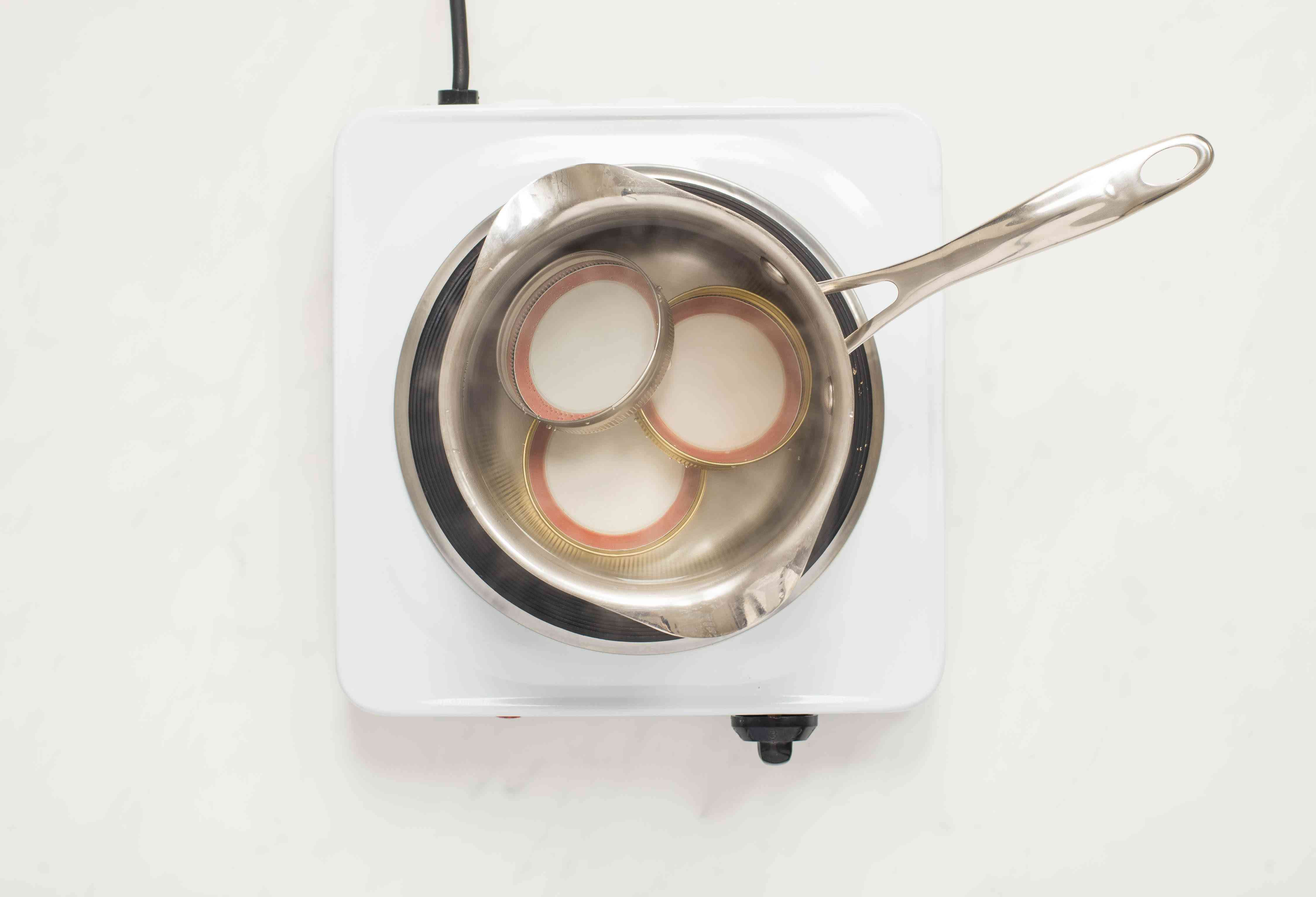 Lids are heated in a small saucepan