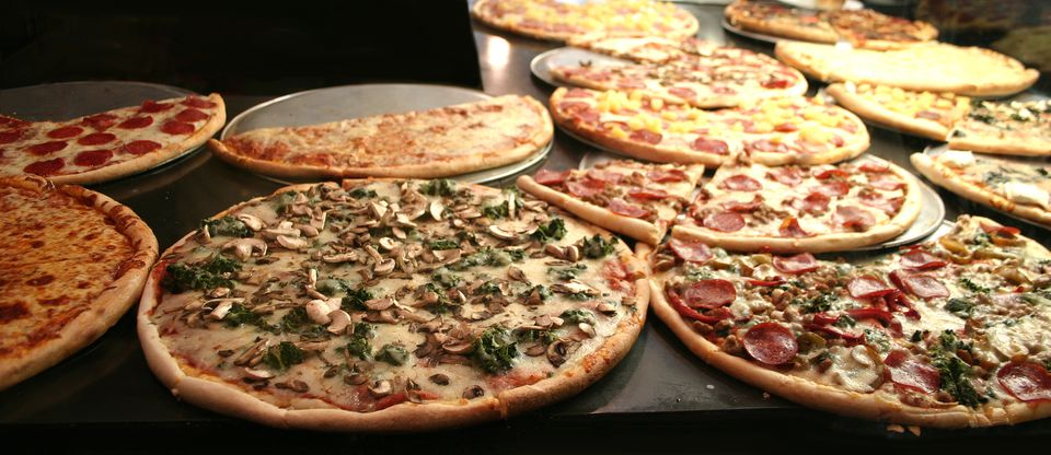 Different New York-style pizzas on a table