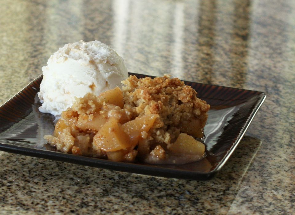 A plate of apple crisp with ice cream