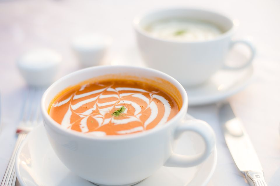 Two cups of tomato bisque soup on table