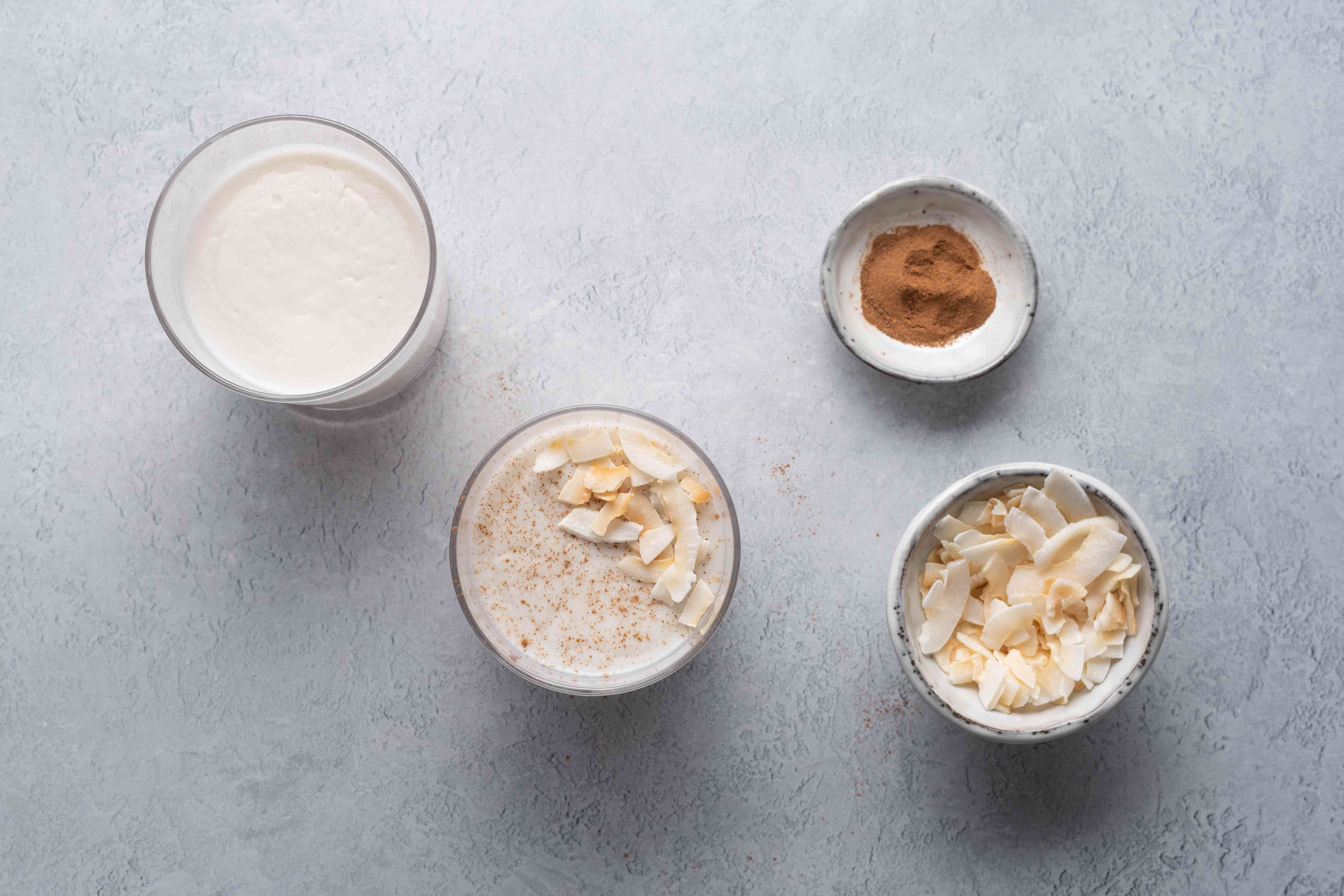 Cups of coconut pudding topped with toasted coconut and cinnamon