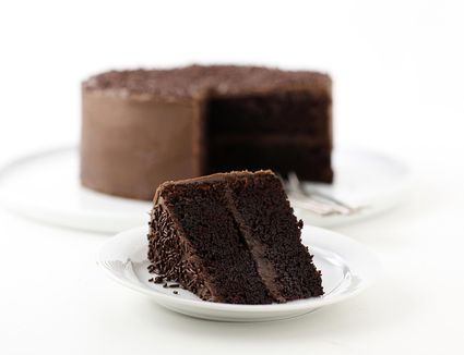 A plate of chocolate cake with a sliced out piece
