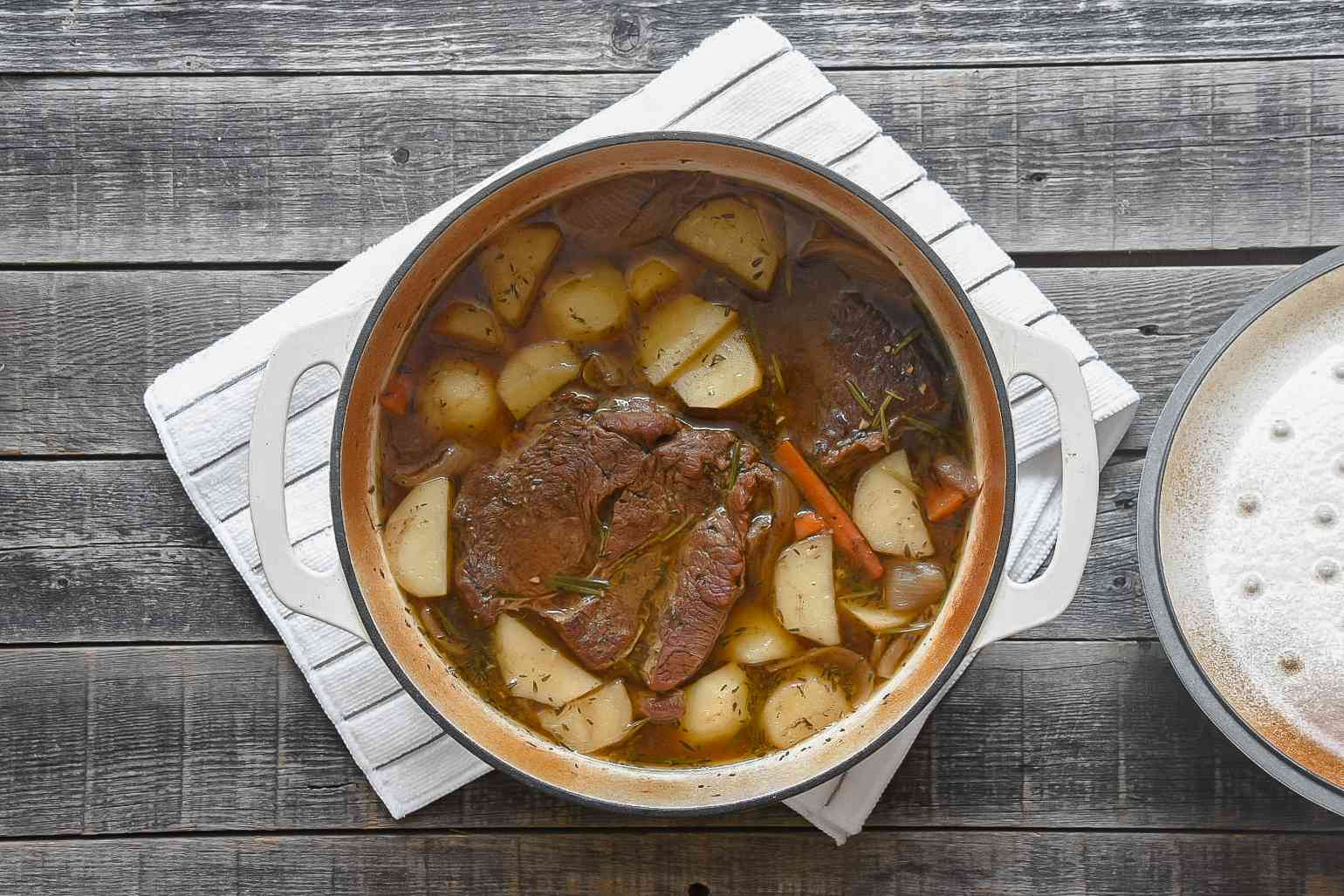Pot roast with potatoes, carrots, onions and herbs in stock, in a large white pot