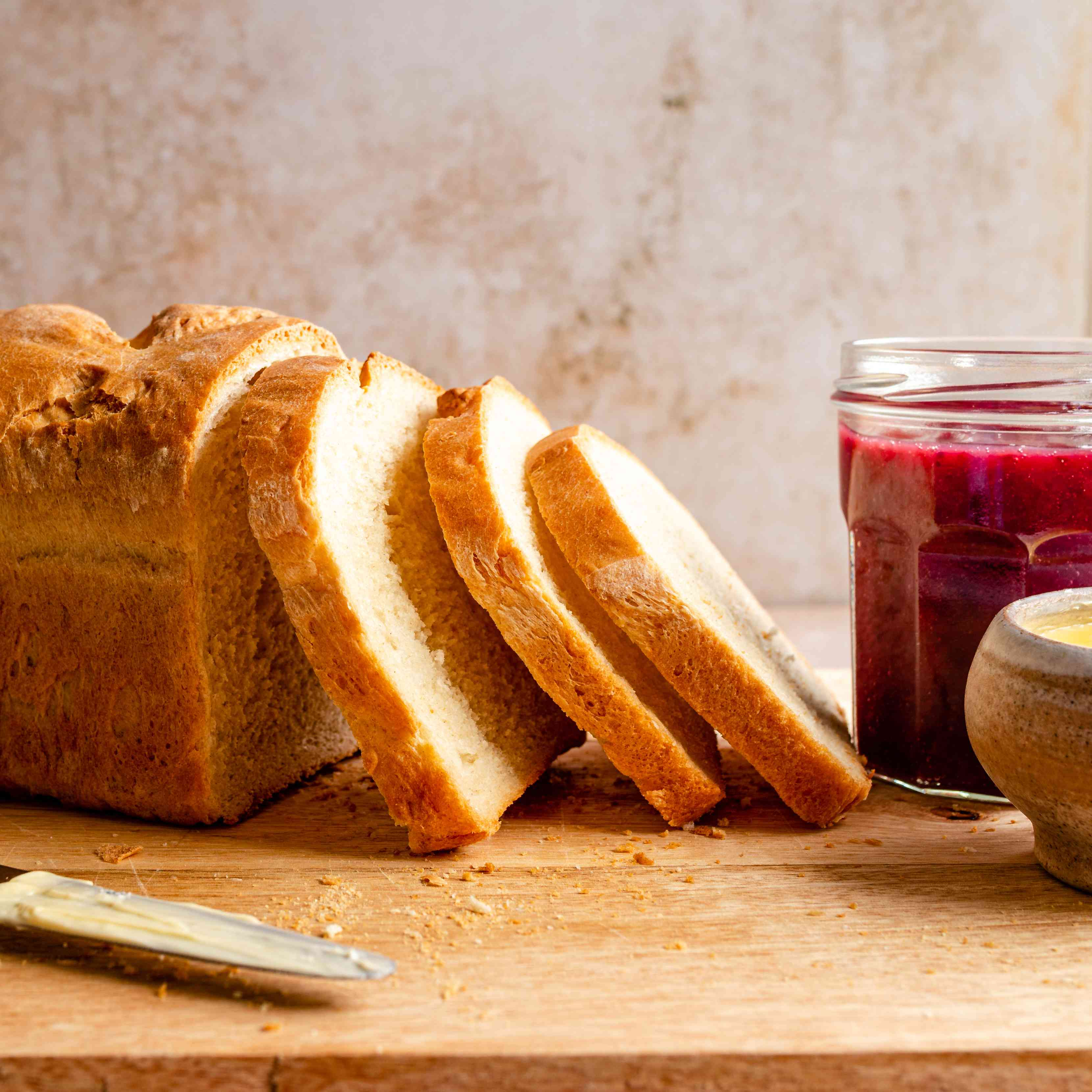 Sliced homemade bread with a jar of berry preserve