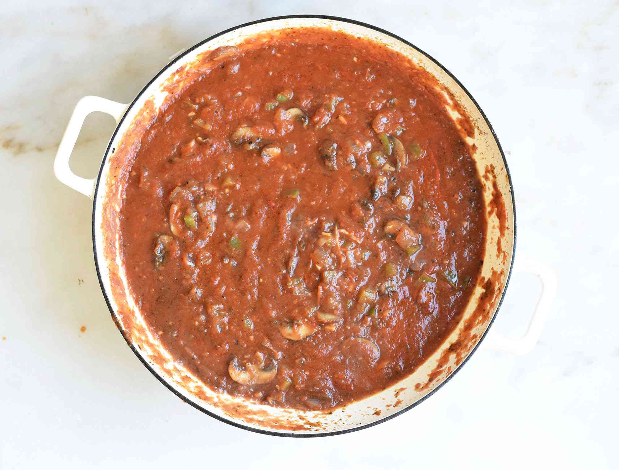 Crushed tomatoes in a pot with cacciatore ingredients