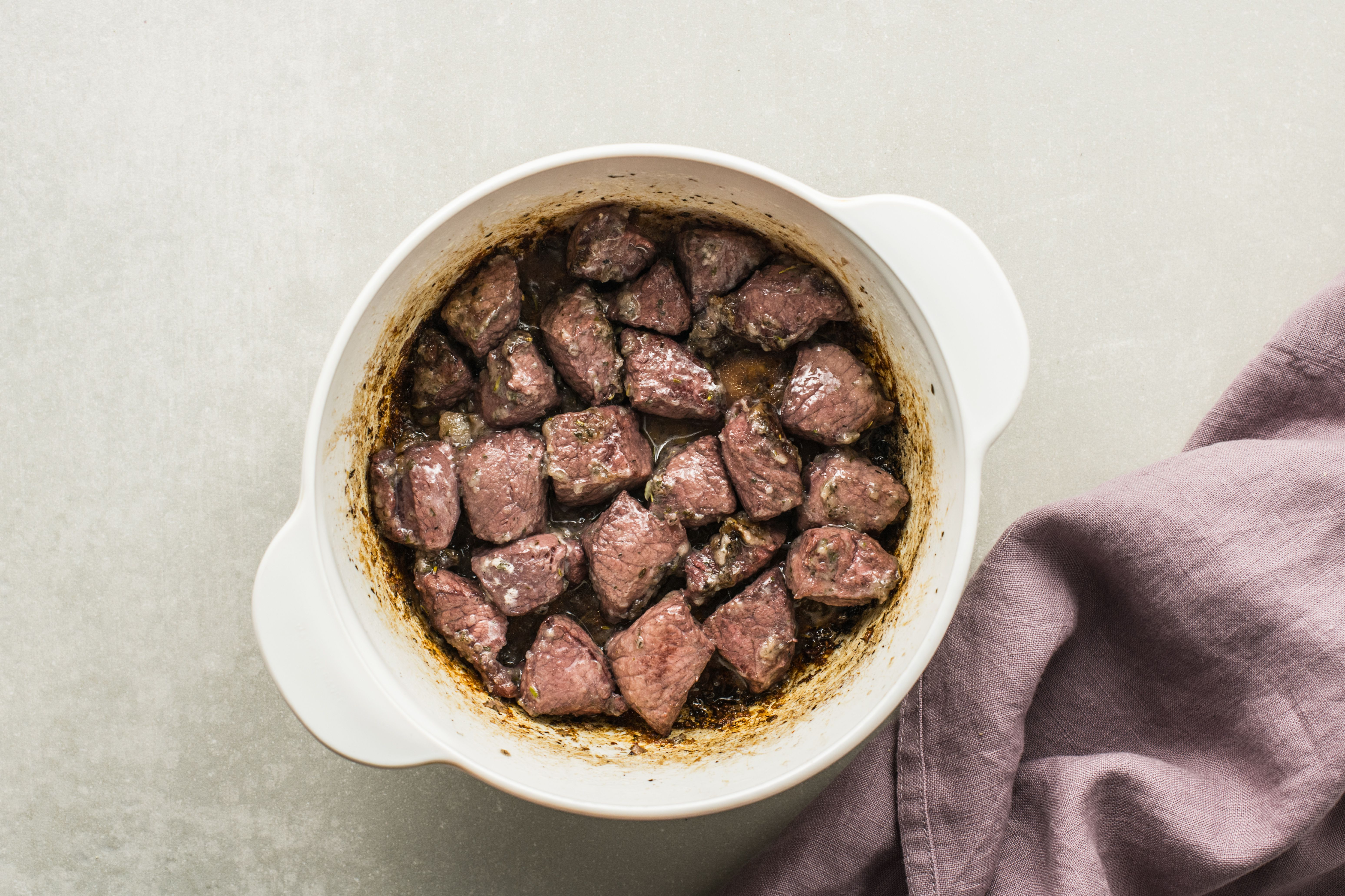 Venison tossed with flour and cooking in remaining bacon grease