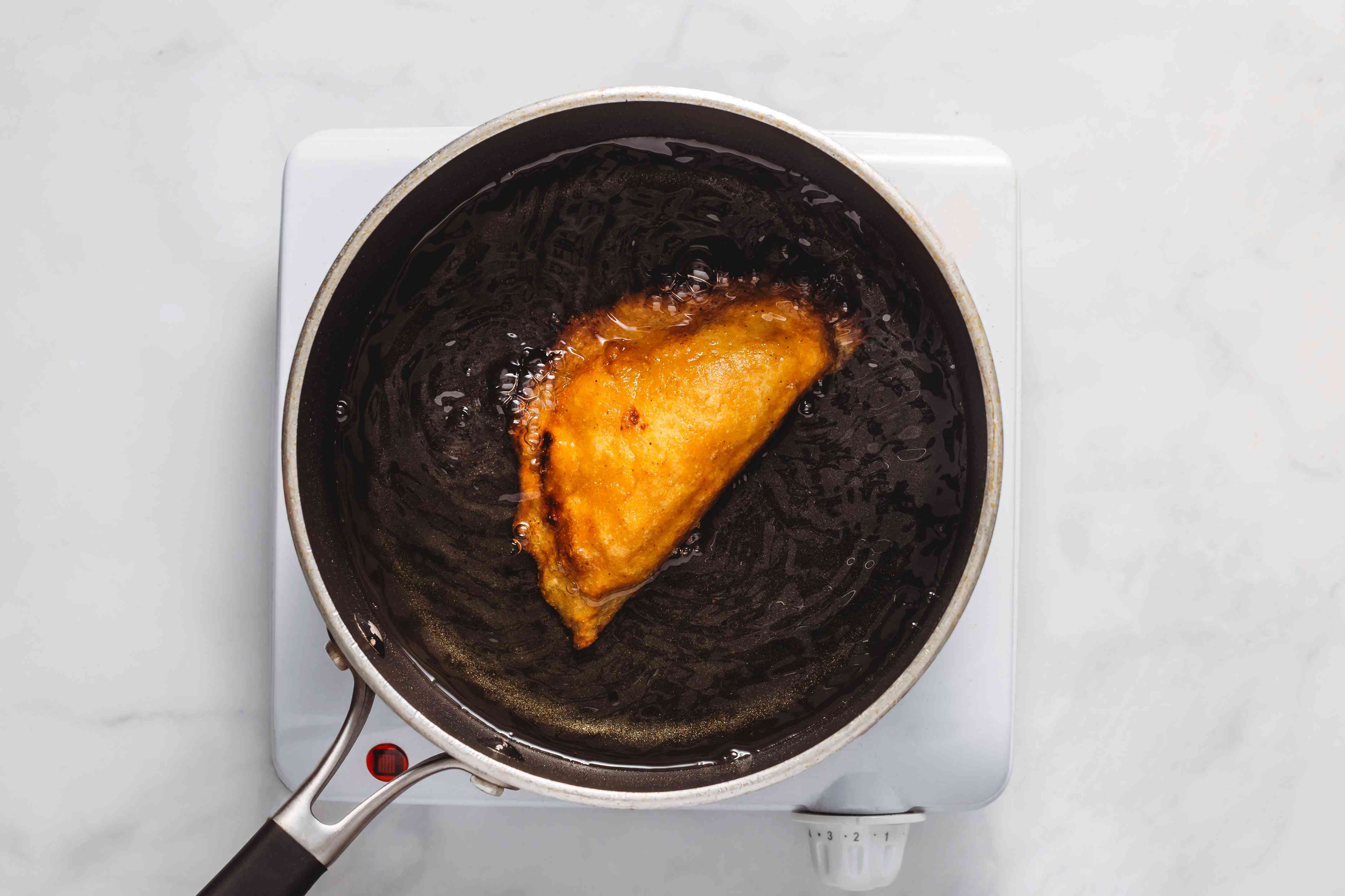 Traditional Fried Mexican Quesadillas frying in a pan with oil