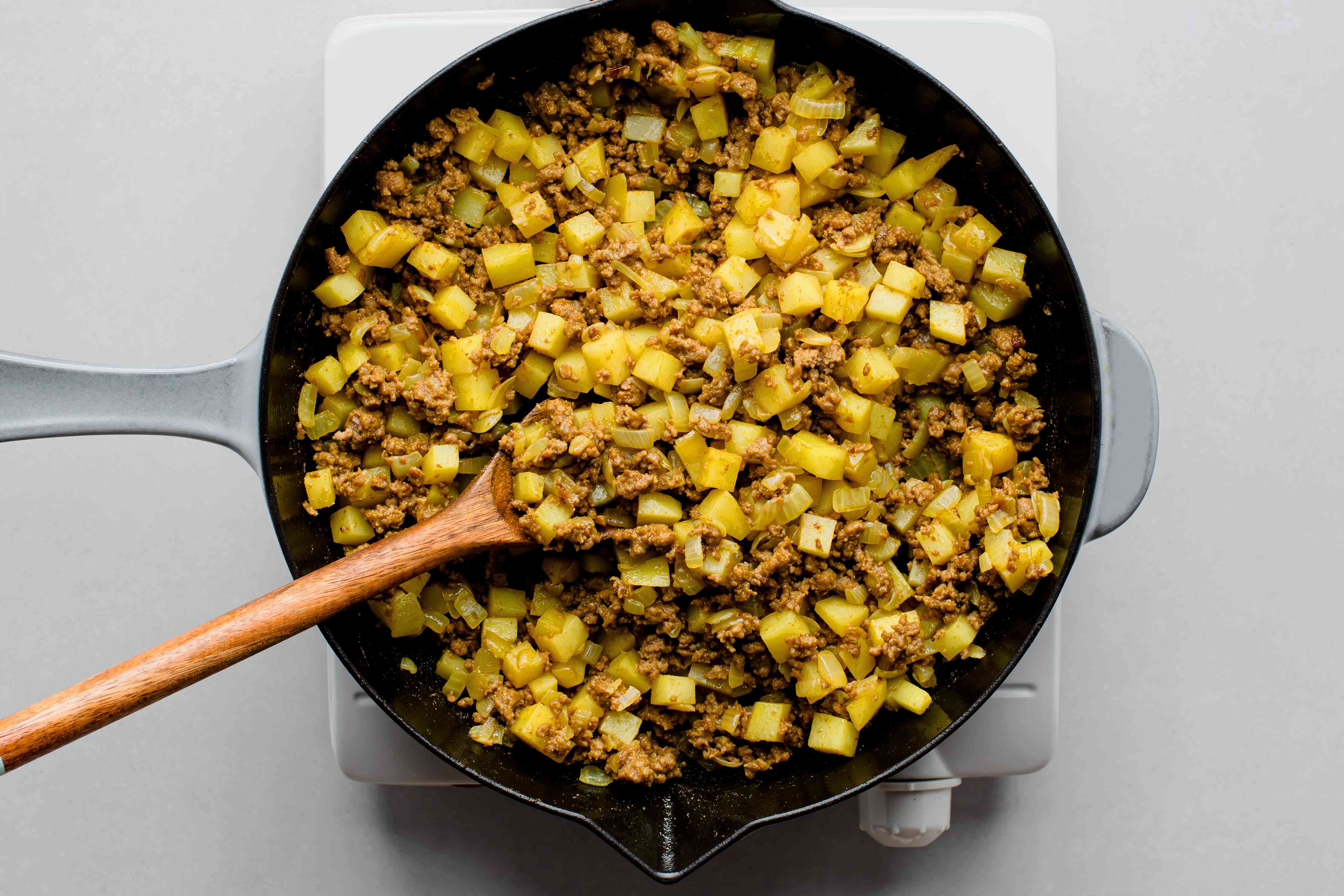 cubed potatoes added to the curry beef mixture in a skillet