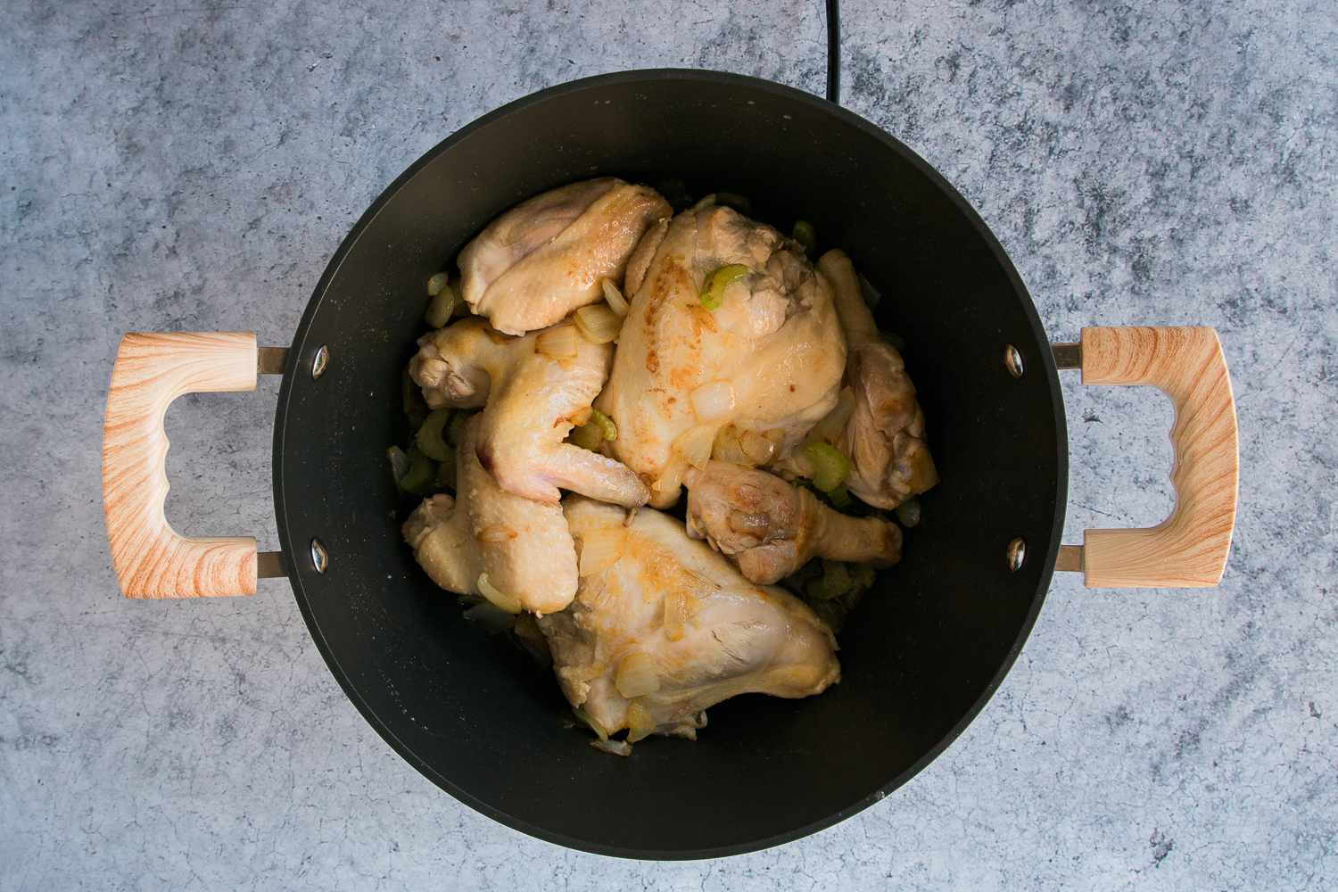 celery, onion, and chicken and brown chicken pieces in a Dutch oven