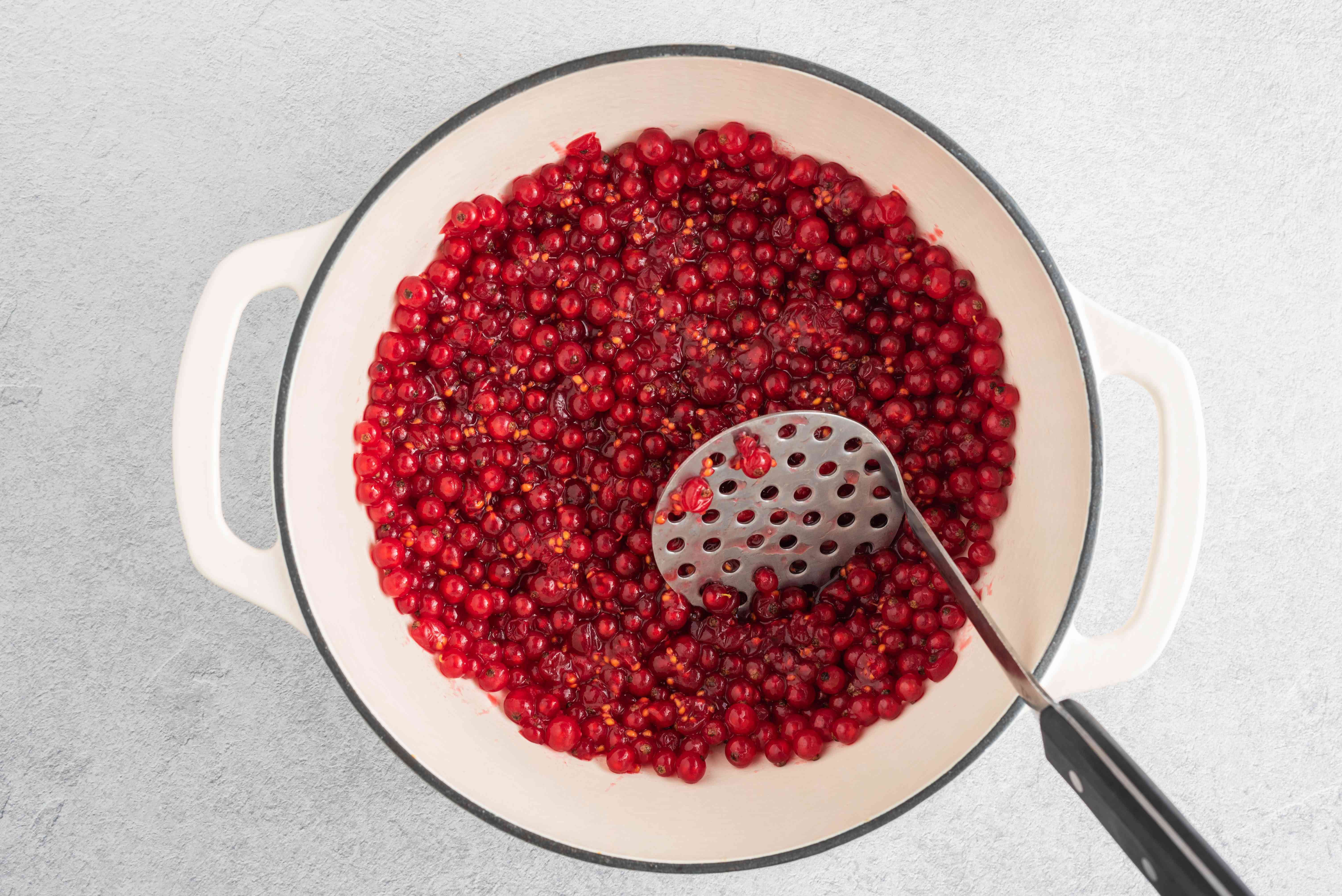 red currant in large white pot with a potato masher