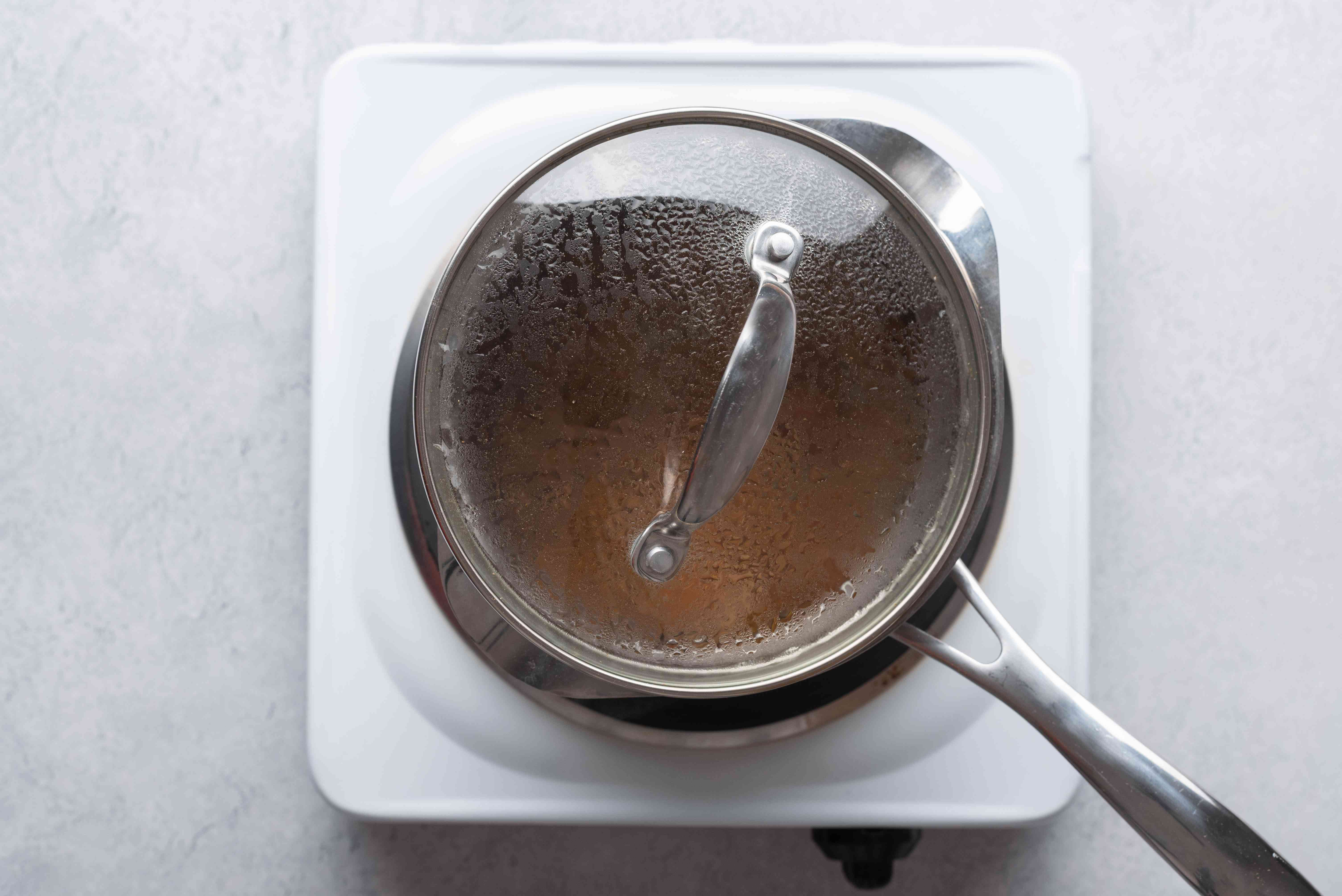 pot with water and apricots, covered on stove top