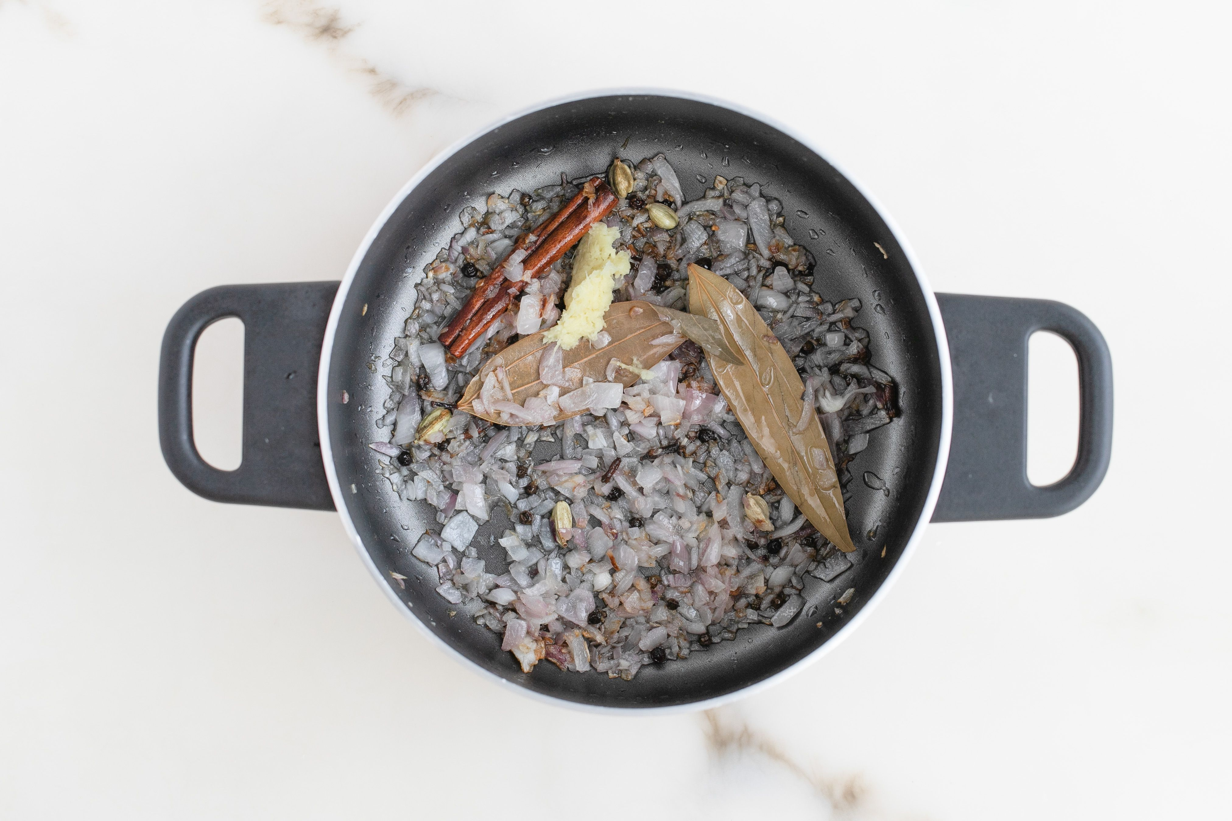Spices and onions frying in a pot