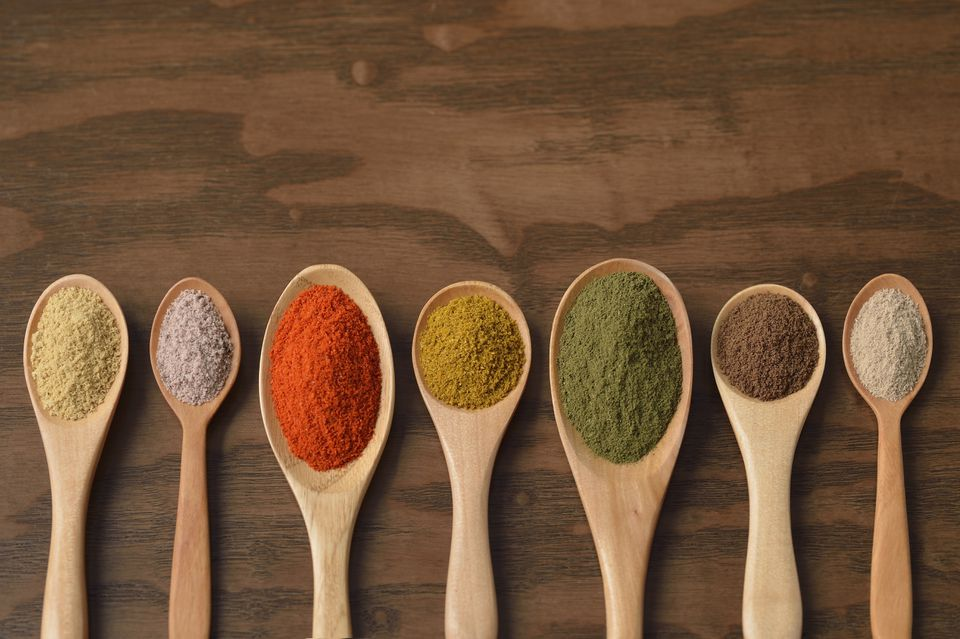 Various colorful spices on wooden spoons