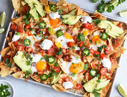 breakfast nachos topped with eggs, cheese, and avocados