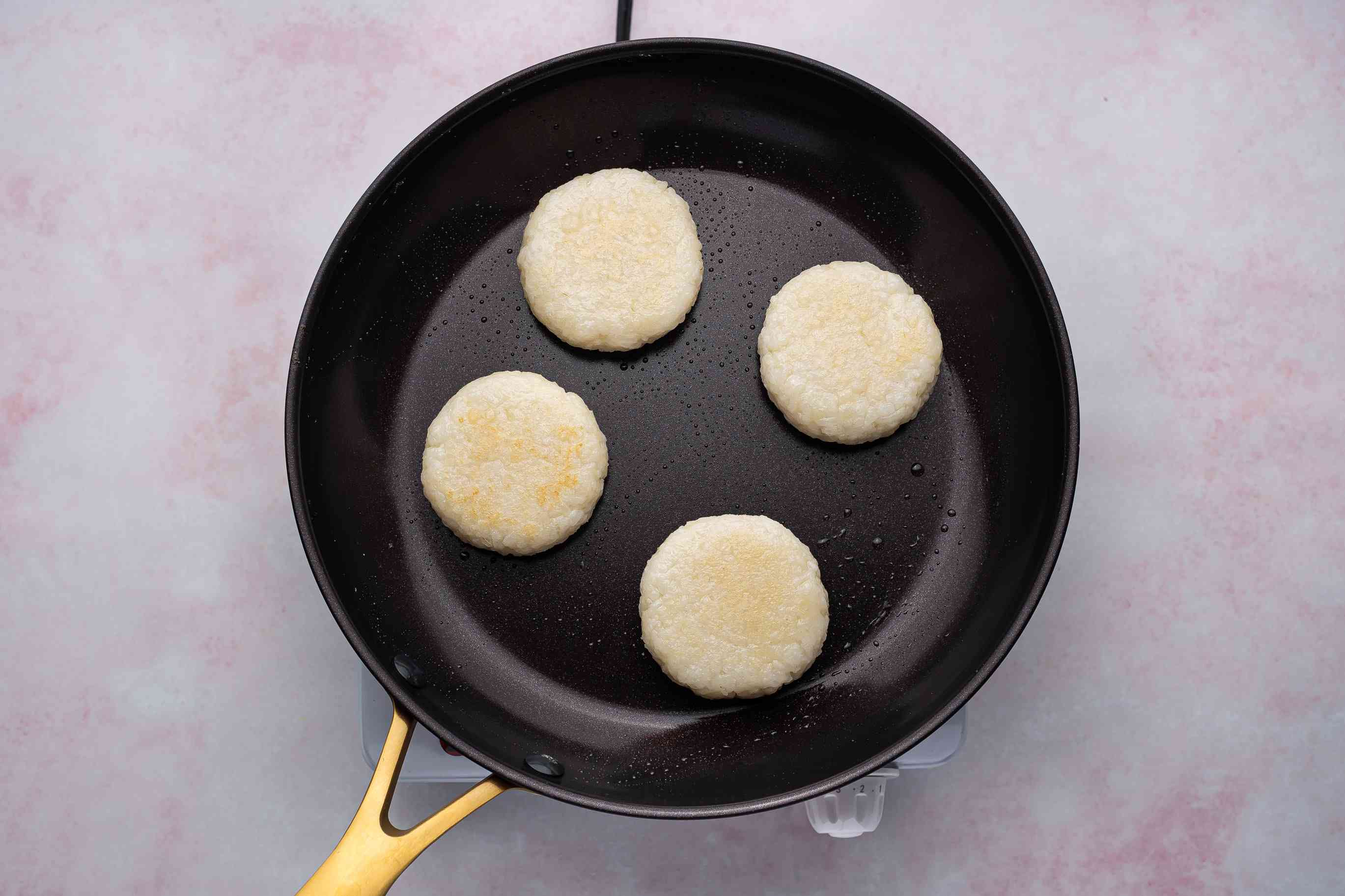 rice cakes cooking in a skillet