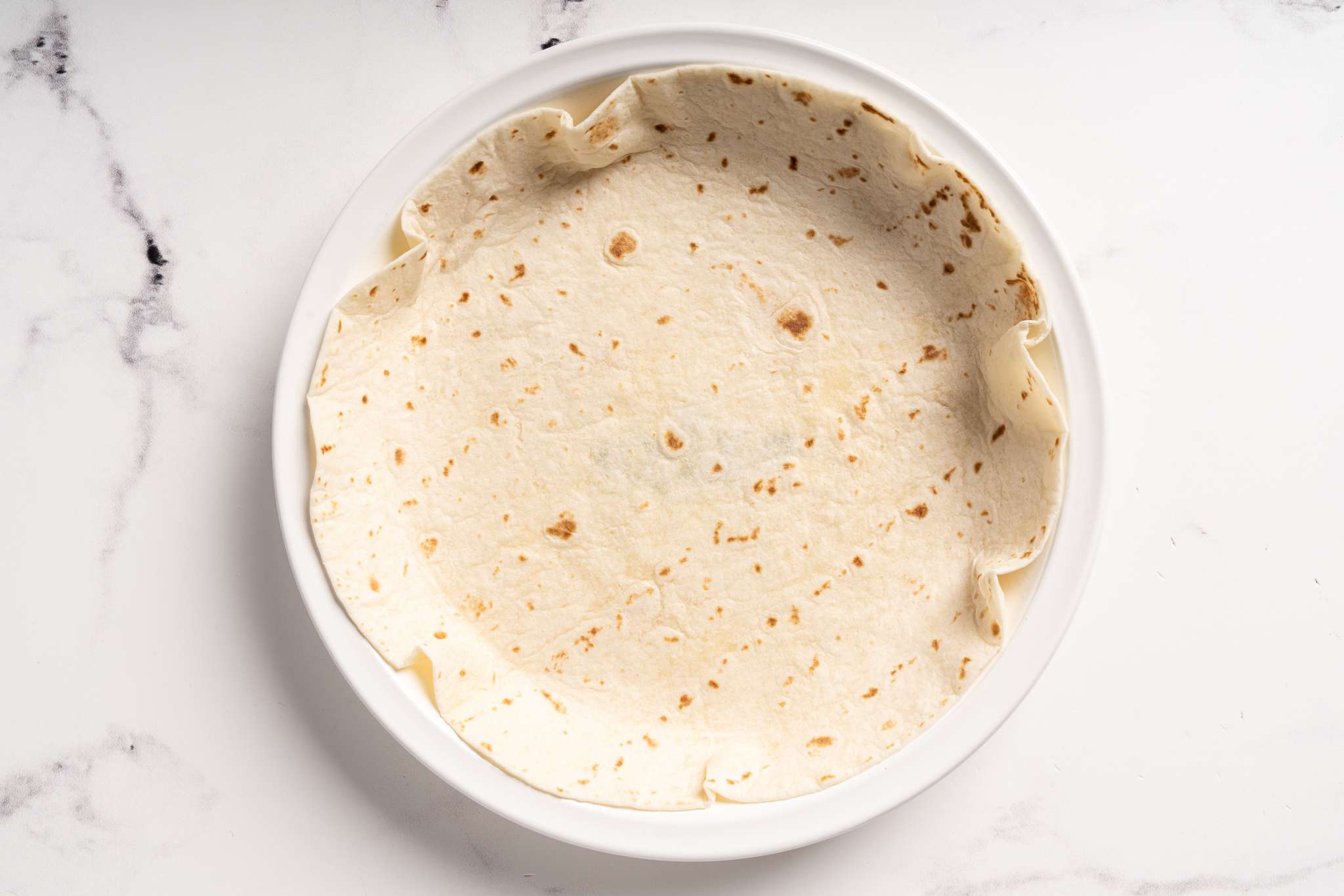 A pie plate filled with a tortilla