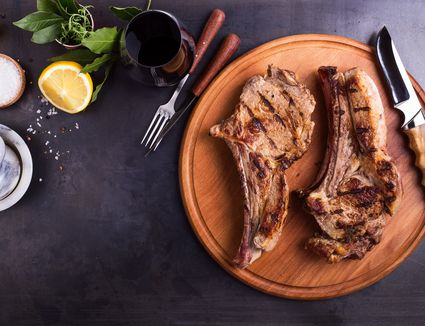 Barbecue bone-in ribeye steak on cutting board