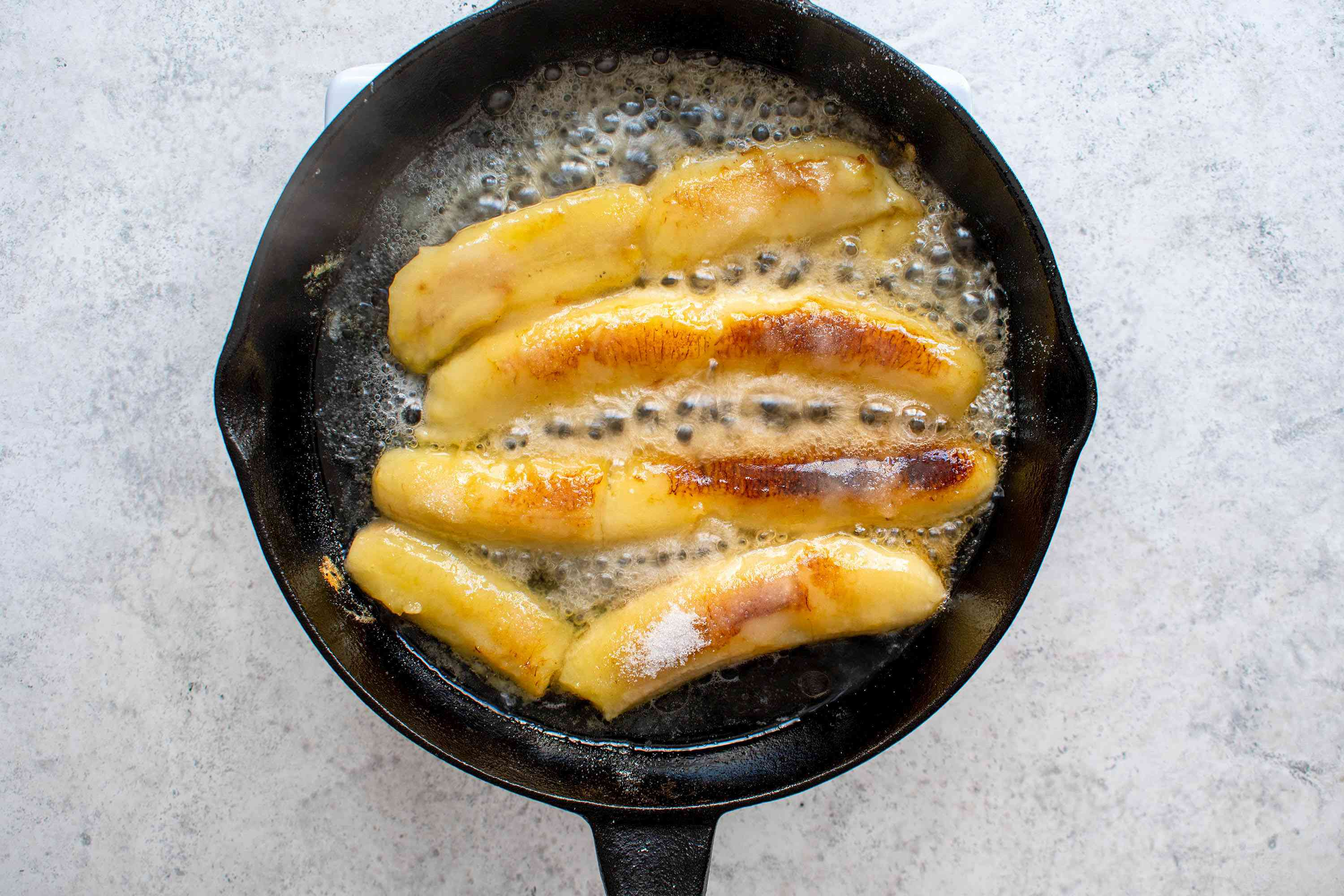 Add the sugar and rum to the bananas in the frying pan