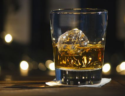 a glass of bourbon with ice on a wooden table