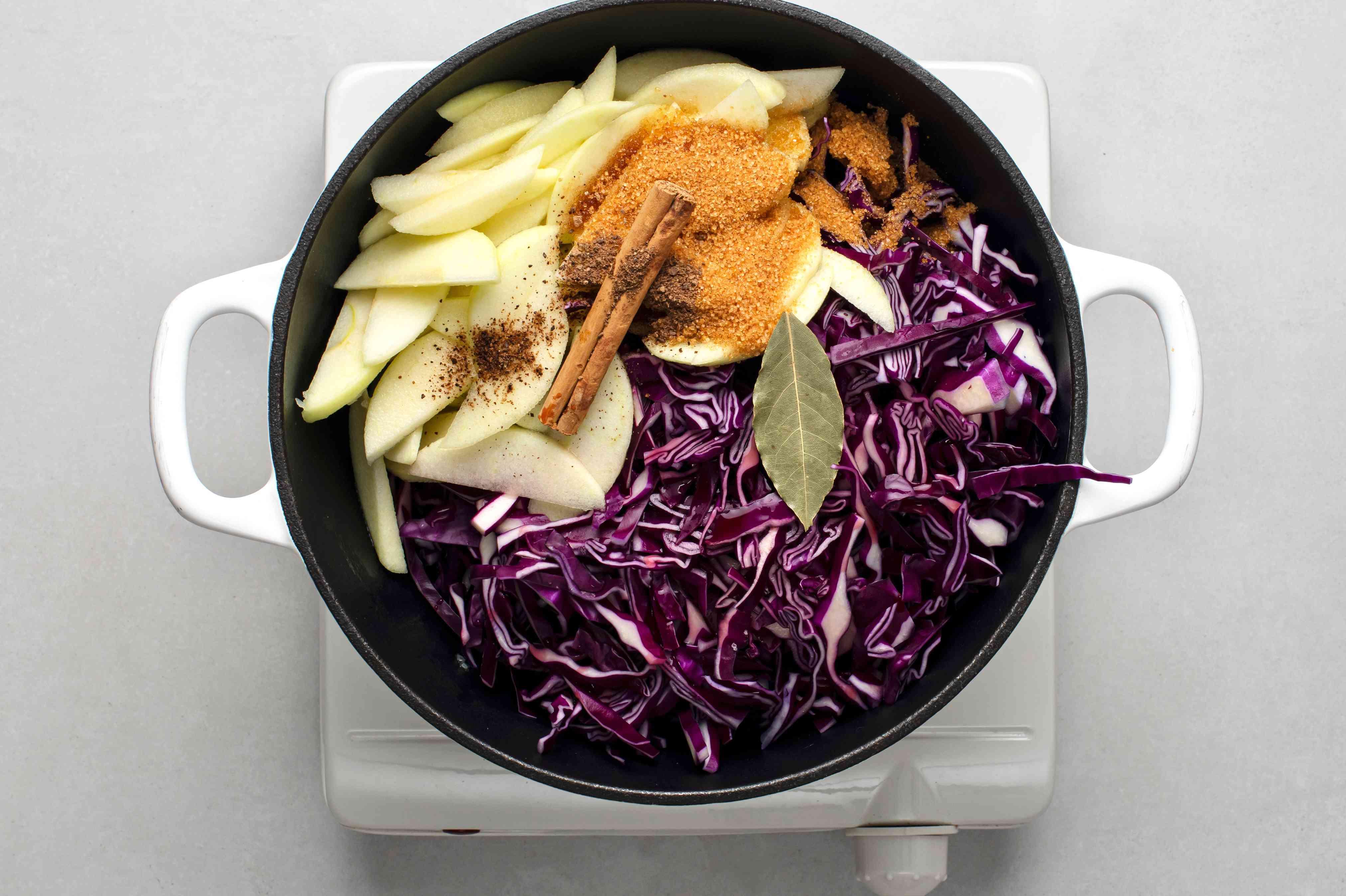 To the onion mixture, add the cabbage, apple slices, wine, vinegar, brown sugar, bay leaf, cinnamon stick, and allspice