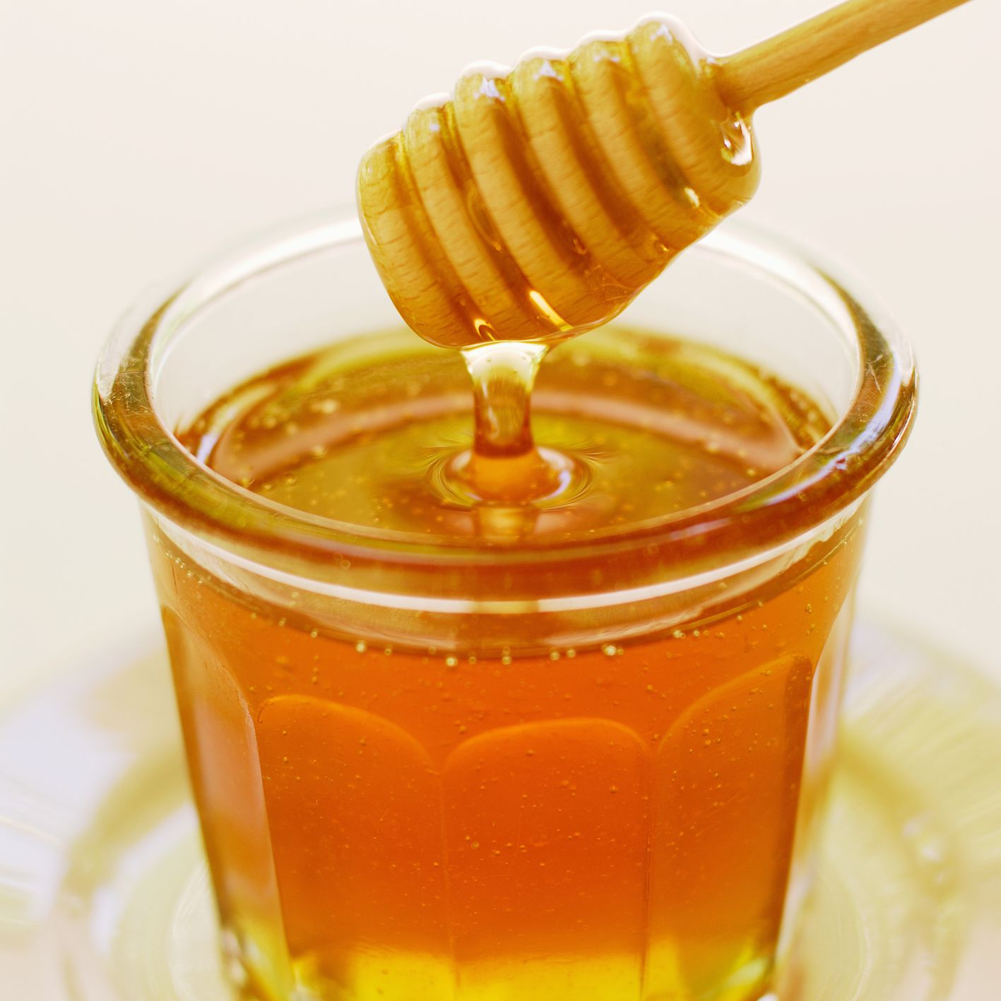 Clover honey in a jar with dipper