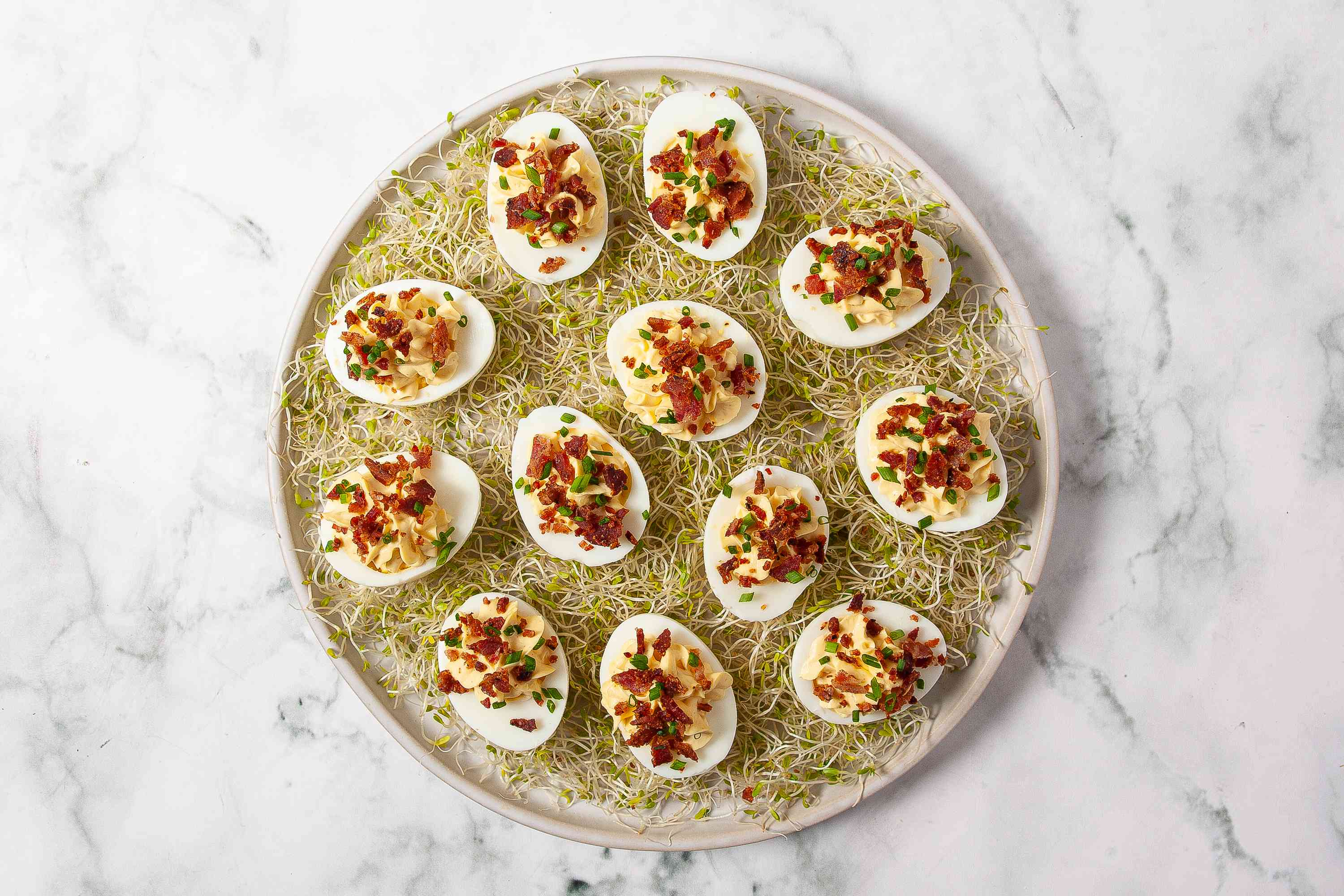 Deviled eggs with bacon and chives on a platter with alfalfa sprouts