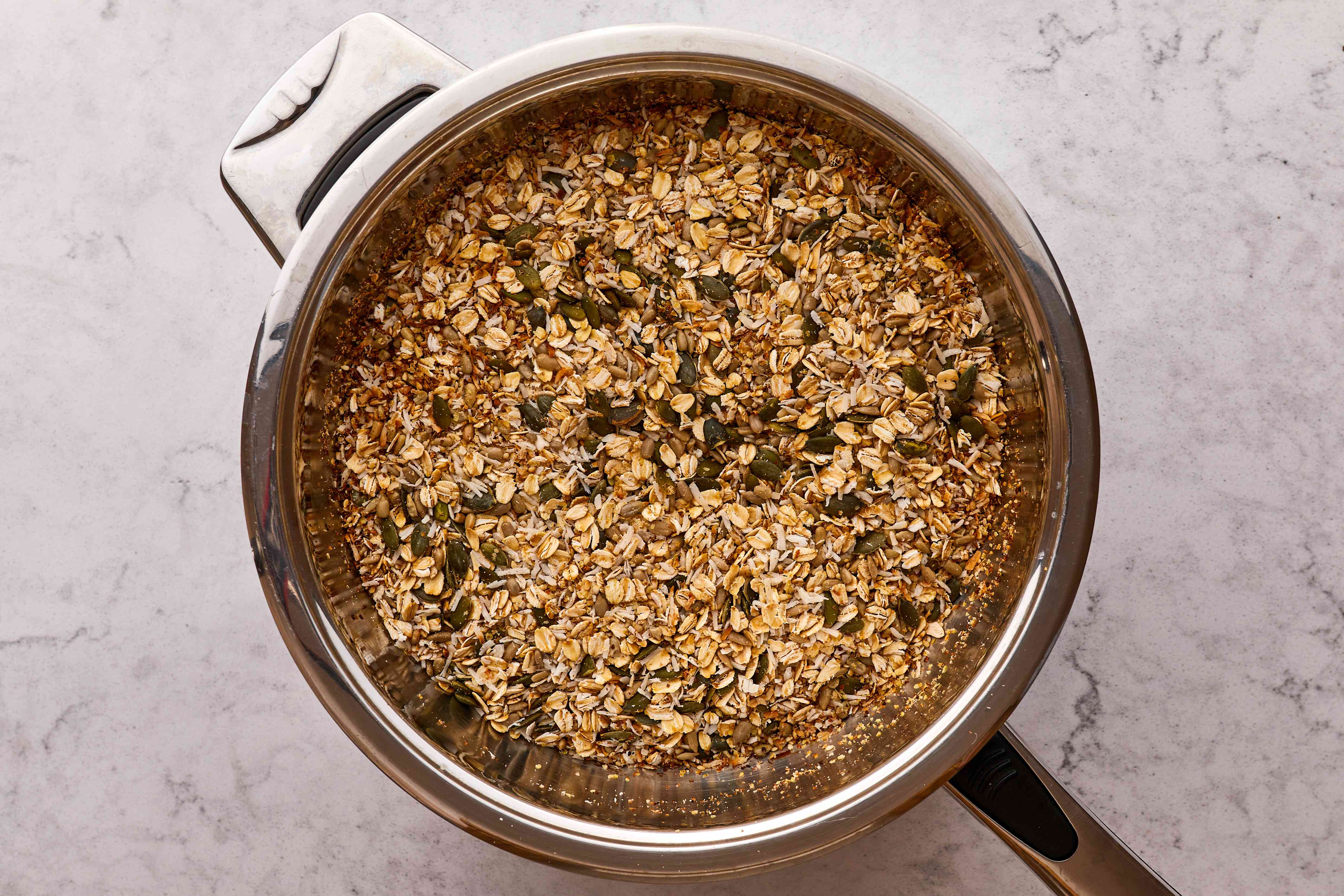 rolled oats, unsweetened dried coconut, wheat germ, sesame seeds, sunflower seeds, and pumpkin seeds in a pot