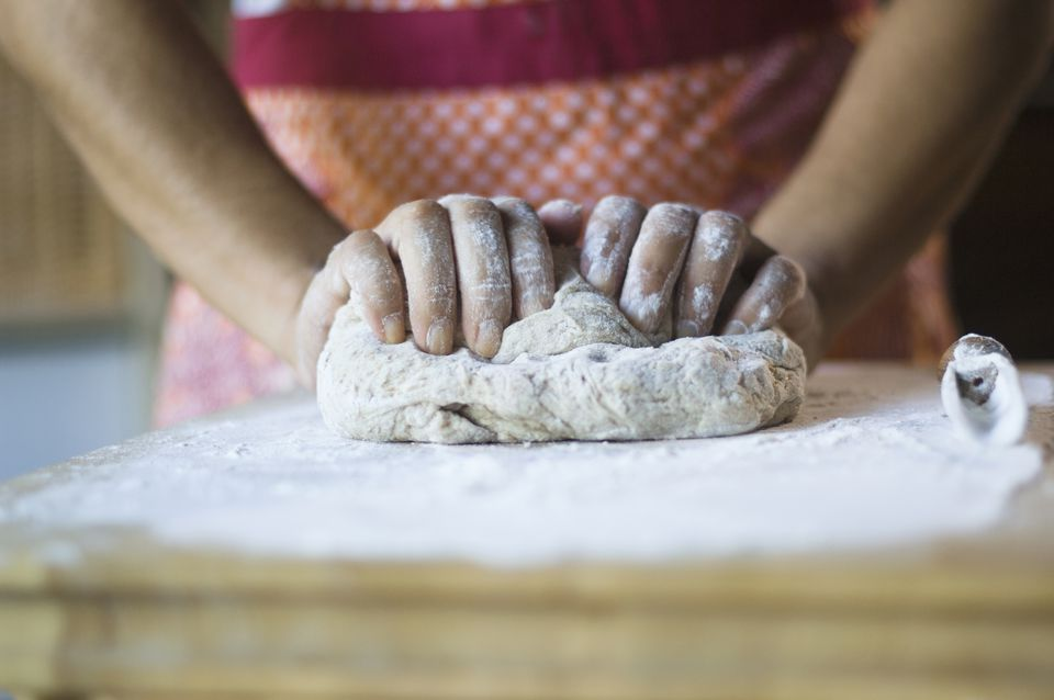 Woman kneading dough in kitchen