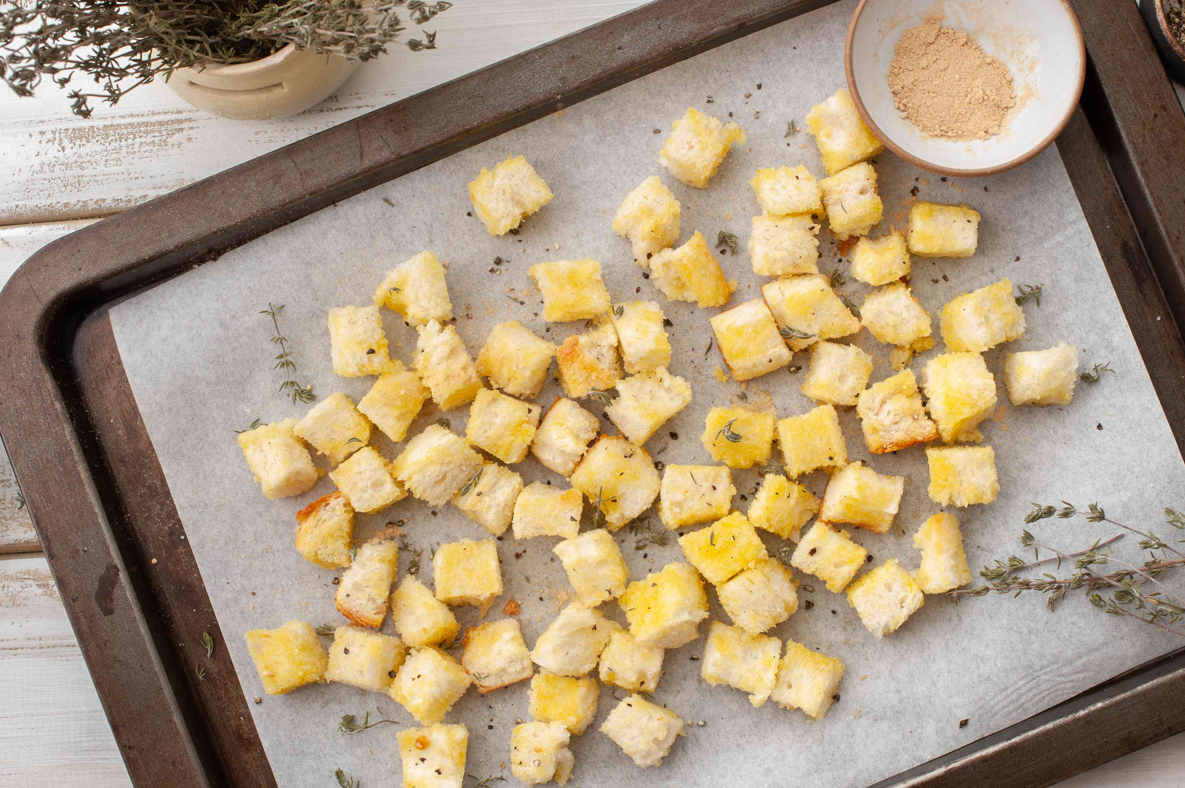 Season croutons with dried herbs on a baking sheet